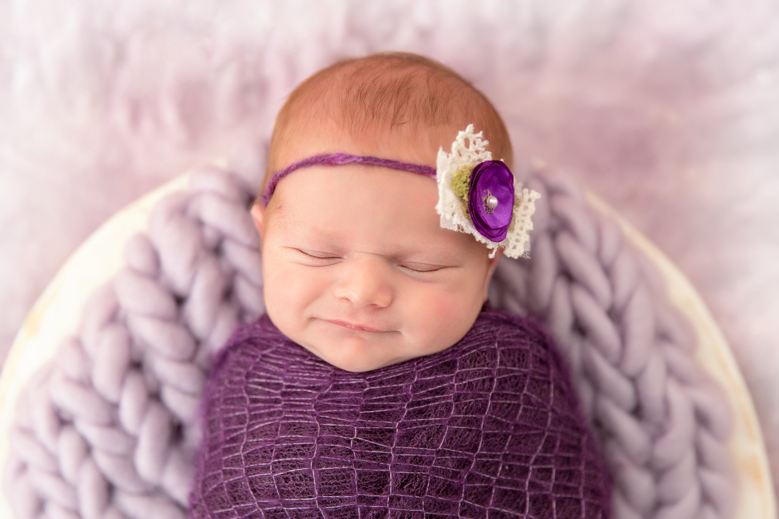 Newborn baby girl smiling. Wrapped in a purple wrap with a purple headband, lying in a white wooden bowl. Newborn baby inspiration photoshoot. Milashka Photography - Calgary Photographer