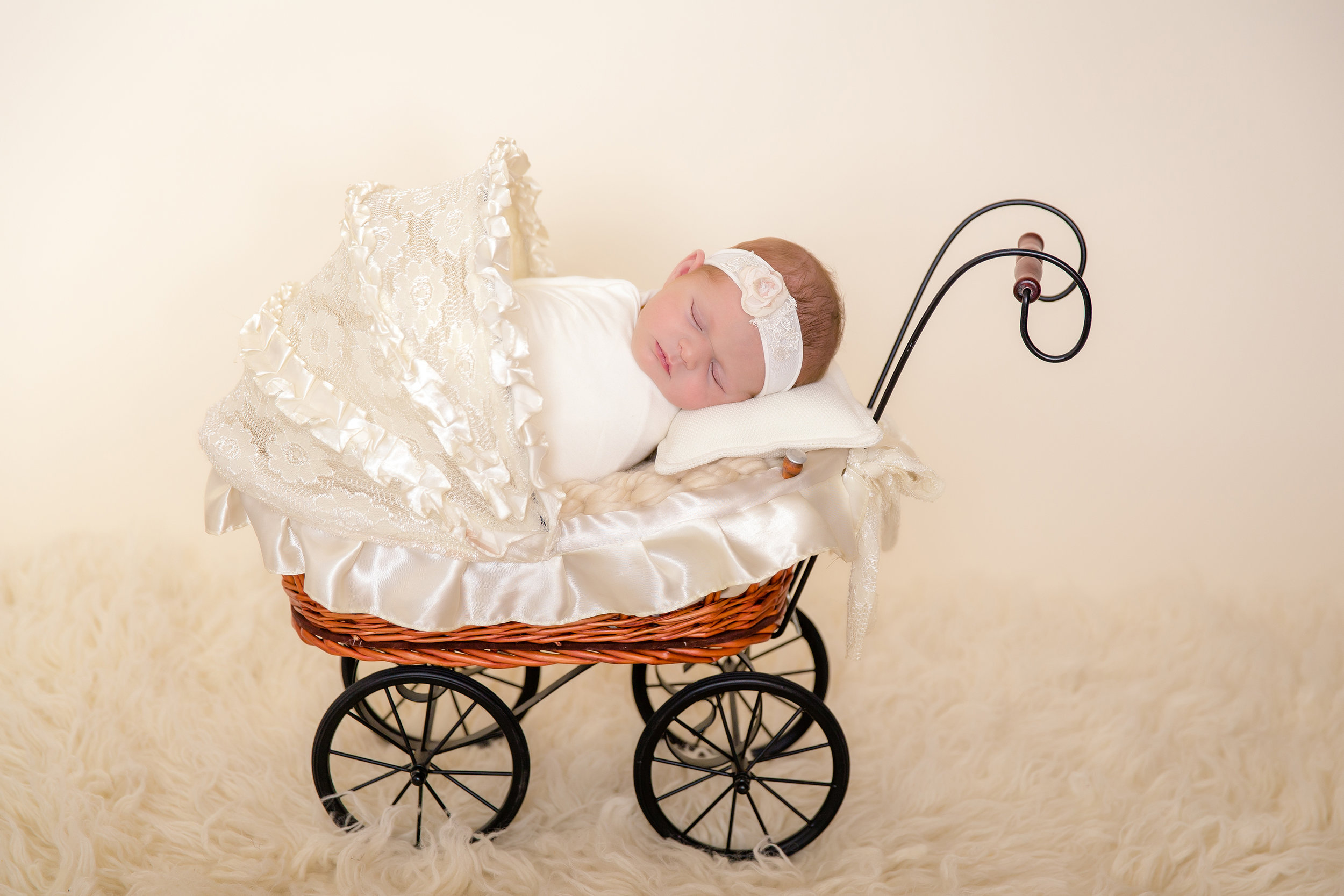 Newborn baby girl sleeping soundly in a cute little stroller, wrapped in a white wrap and wearing a white headband. Newborn Photoshoot ideas. Calgary Newborn Photographer - Milashka Photography.