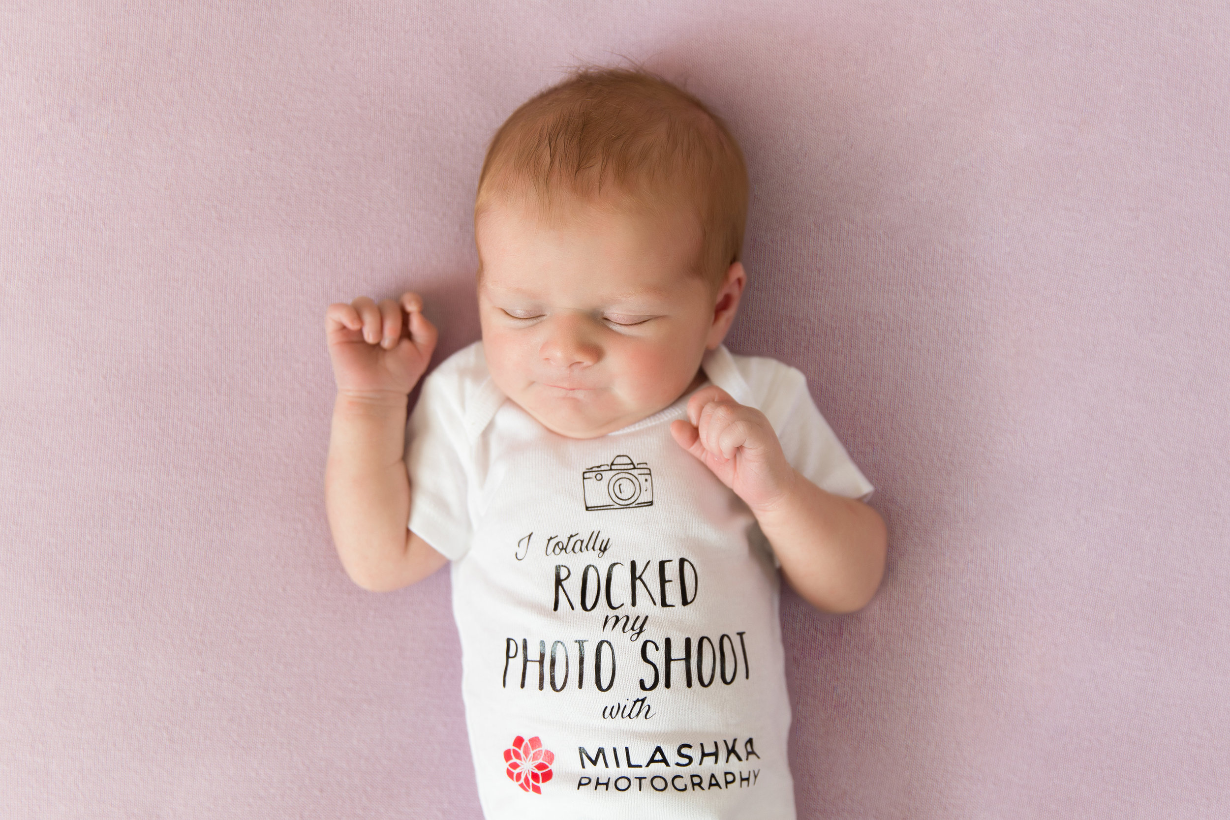 "Newborn baby girl is wearing a onesie that reads: ""I totally rocked my photo shoot with Milashka Photography"". Gift ideas for newborn clients. Calgary Newborn photographer - Milashka Photography."