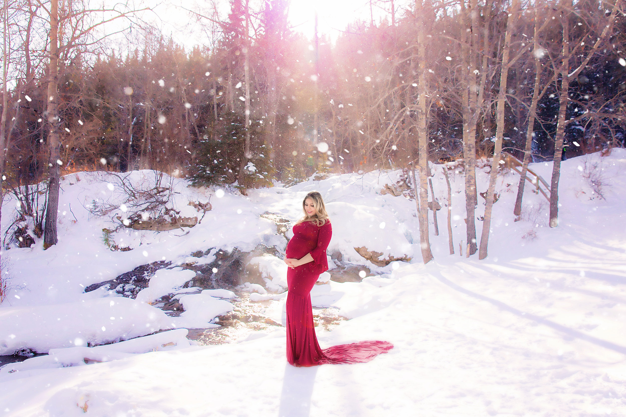 Beautiful mom-to-be is standing on a snow wearing a red gown in the middle of a winter. Calgary Maternity Photographer - Milashka Photography.