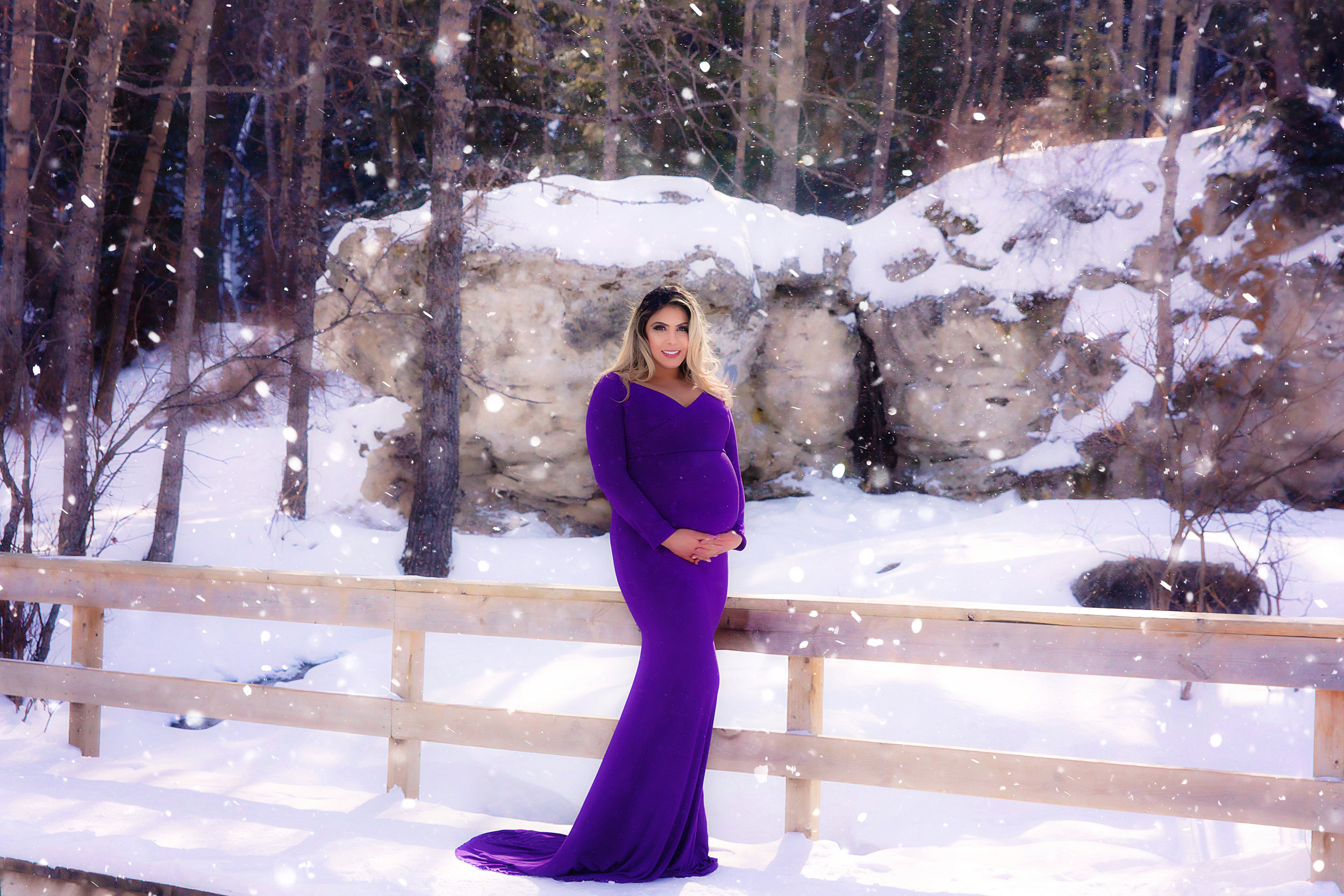 Stunning mom-to-be in a purple gown standing on a bridge and smiling at the Big Hills Spring Provincial Park. Calgary Maternity Photographer - Milashka Photography. Winter maternity photoshoot idea.