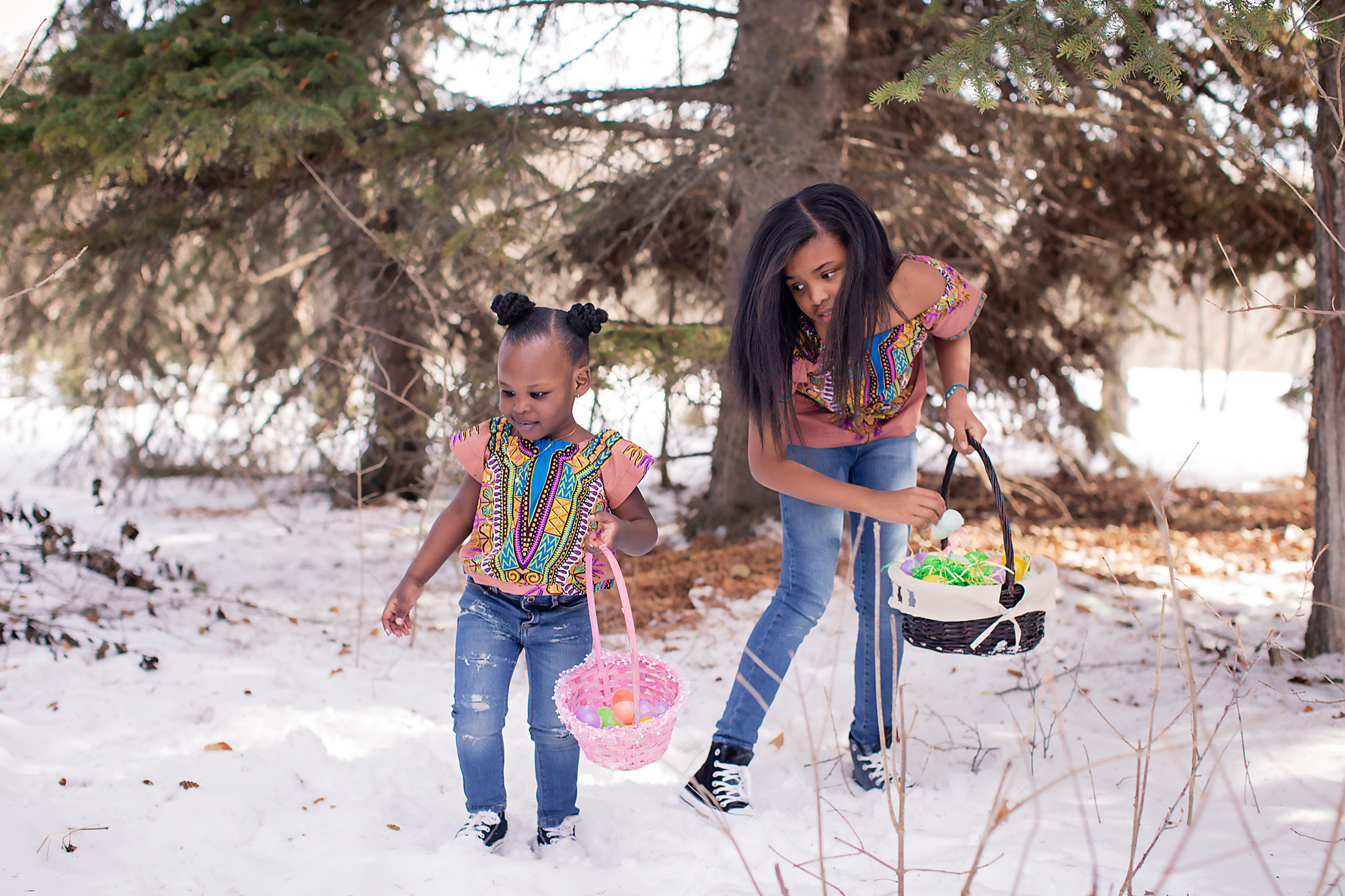 Easter egg hunt in the woods. Two sisters in matching clothes holding baskets and collecting Easter eggs. Calgary children photographer - Milashka Photography