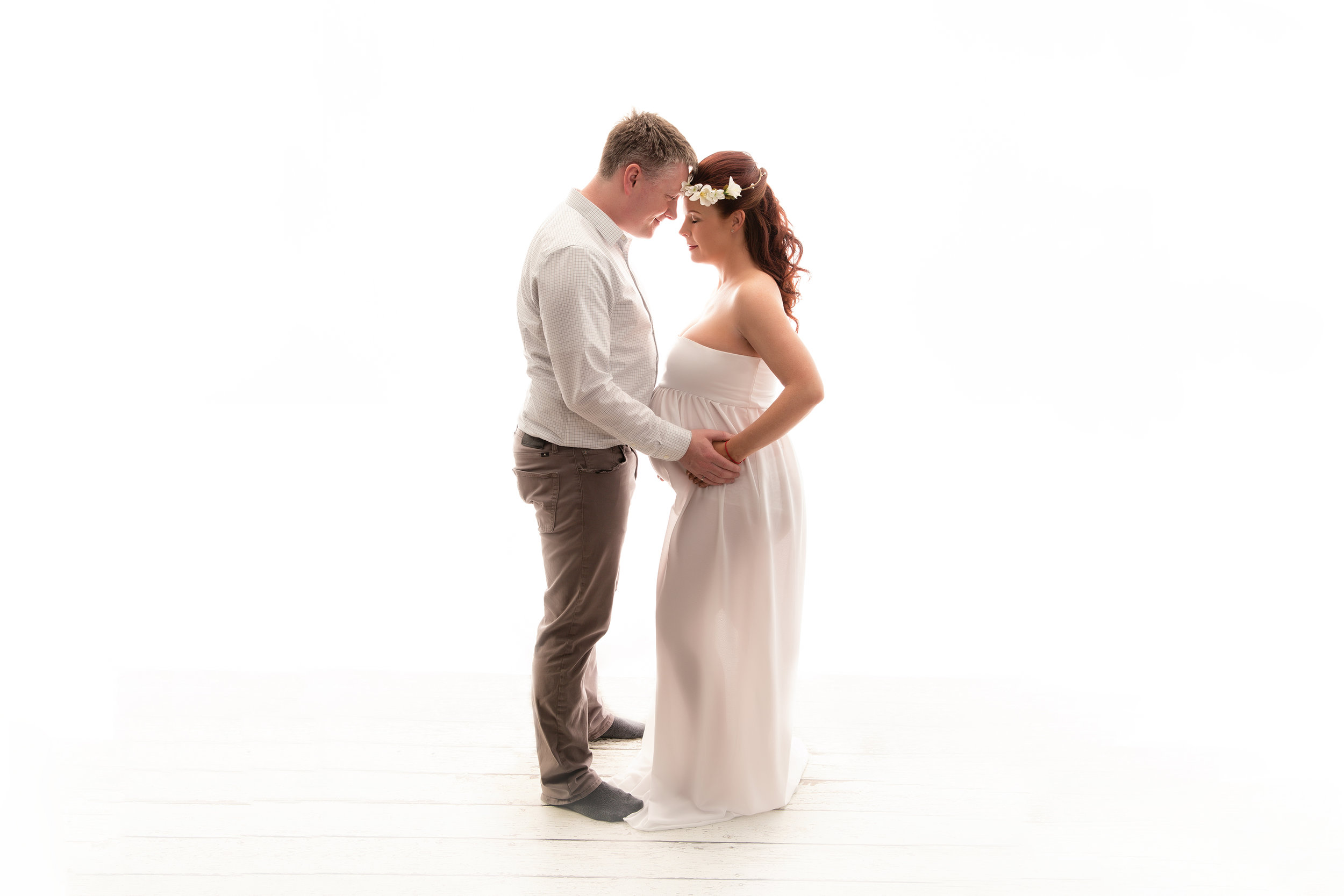 Expectant couple posing in this backlit image. Mom to be is wearing a white gown. Maternity Photoshoot ideas. Calgary Maternity and Newborn photographer - Milashka Photography