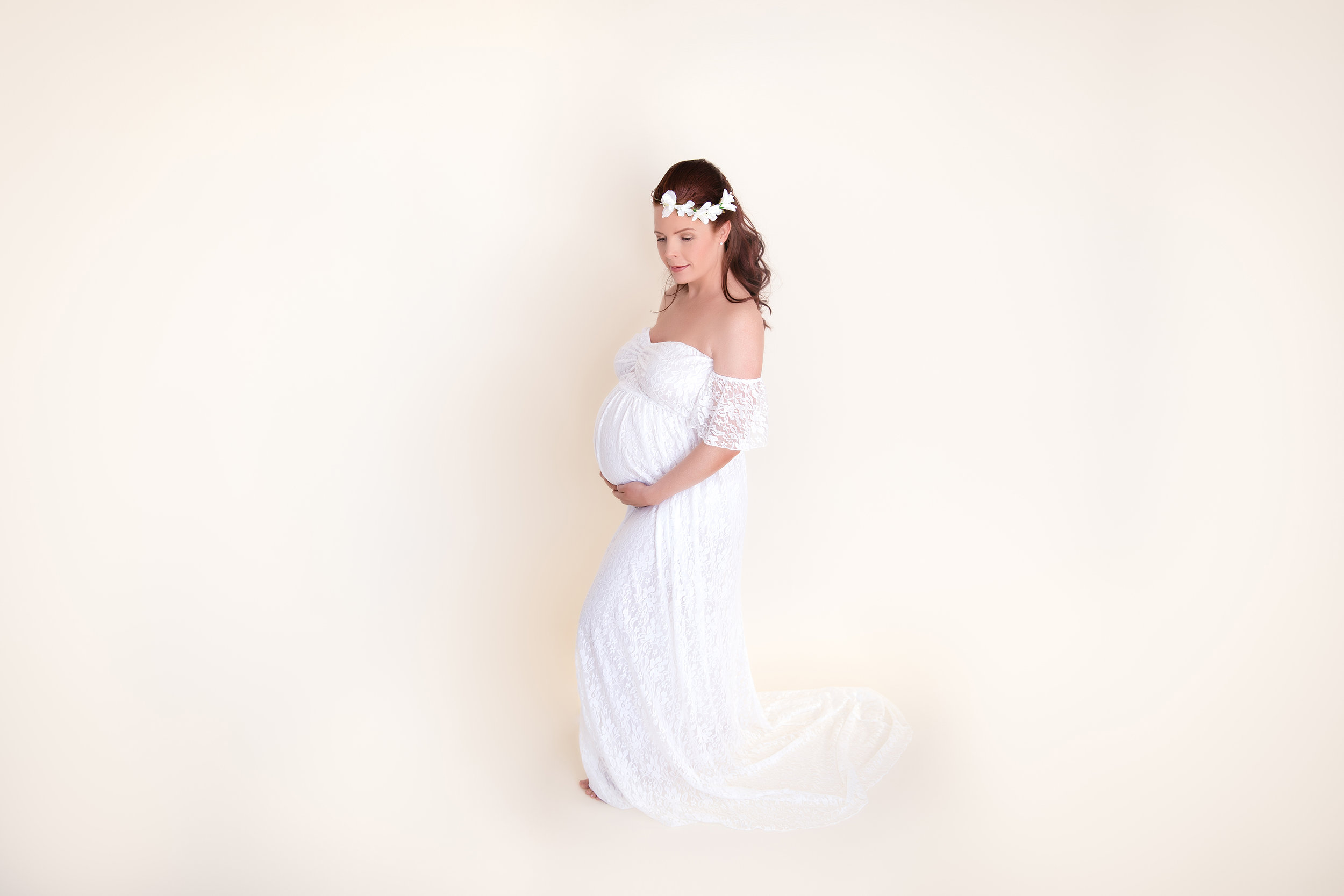 Mother to be is wearing a white gown - maternity photoshoot ideas - Calgary maternity photographer