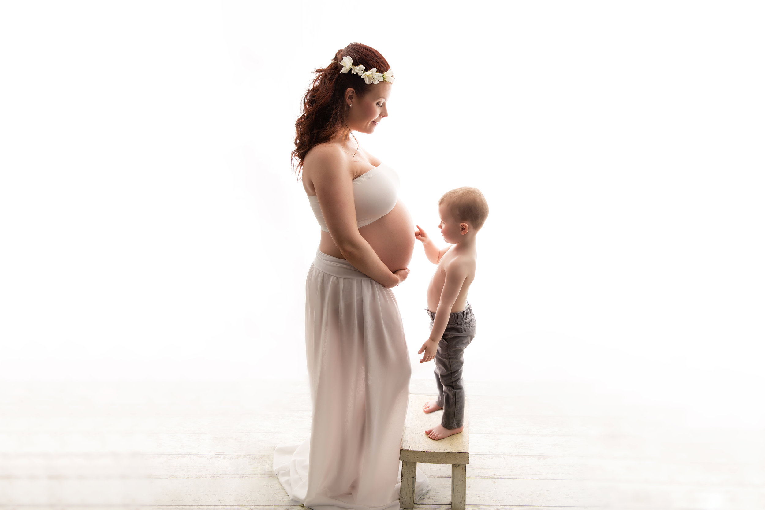 Mom-to-be and her toddler son are posing for this indoor maternity session. Calgary photographer.