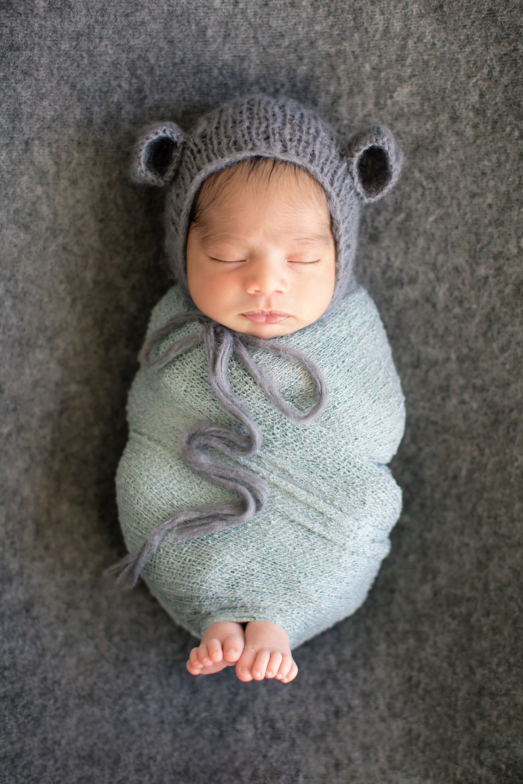 Baby boy wrapped in a grey wrap with little toes sticking out. Back pose - newborn photography. Calgary Photographer
