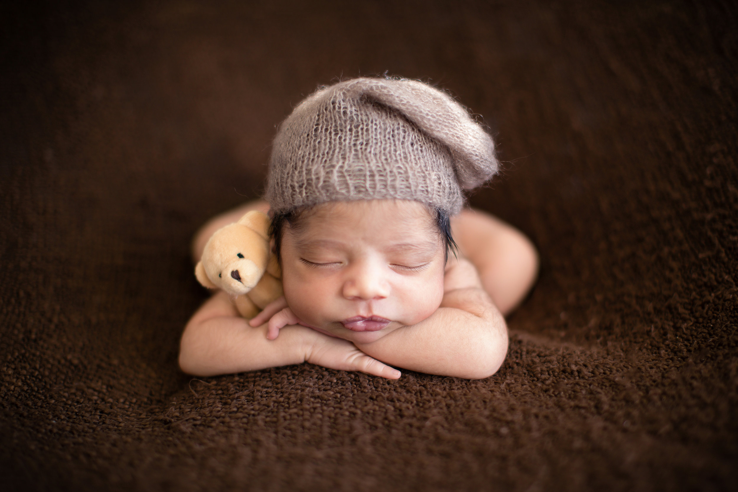 Baby boy sleeping soundly on a beanbag. Hands on chin pose - newborn photography. Calgary Photographer