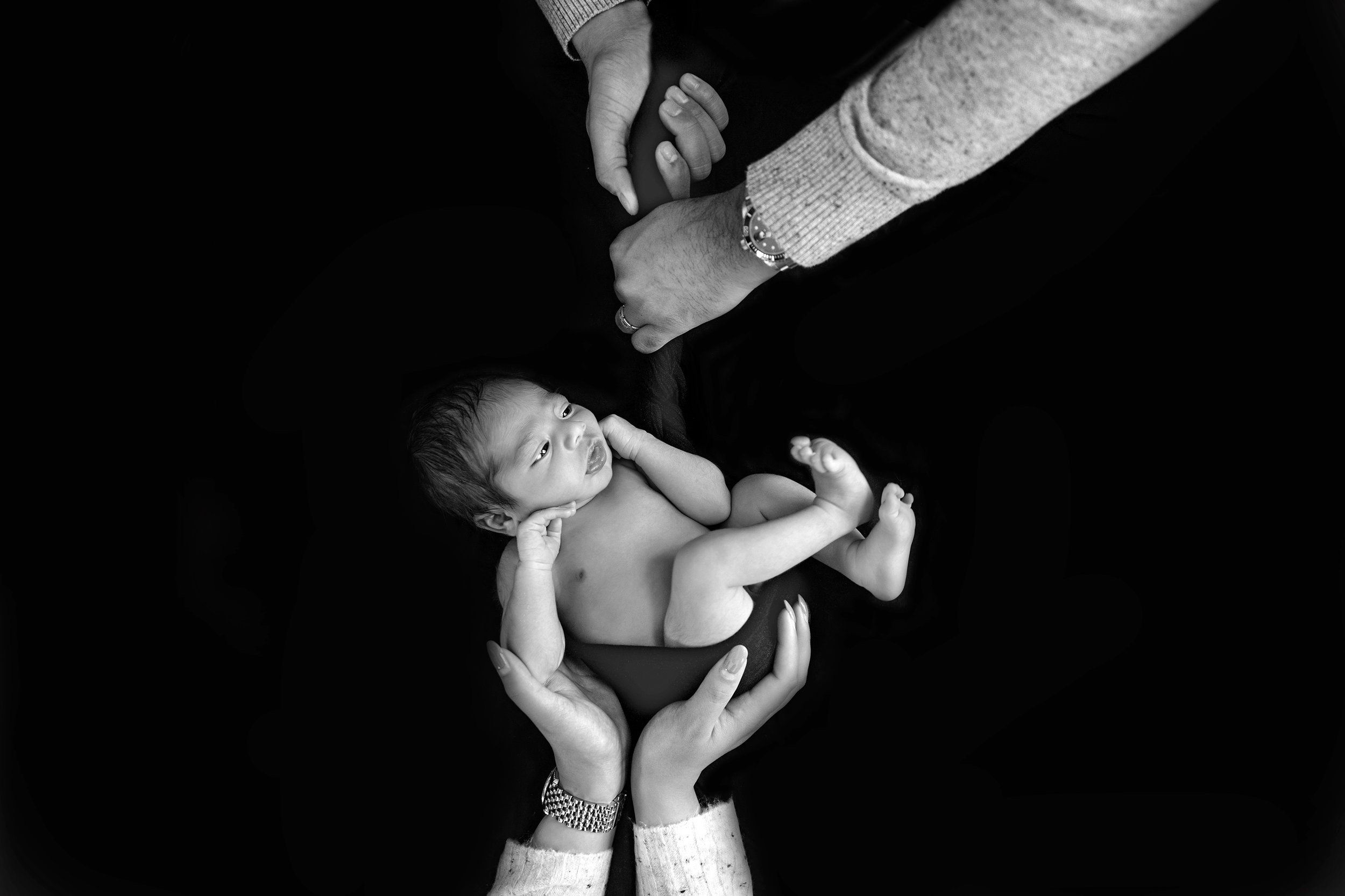 Safe in parents' hands. Baby boy is posed on a beanbag with a black backdrop and parents' hands are keeping him safe. Newborn photography ideas. Calgary baby and newborn photographer - Milashka Photography