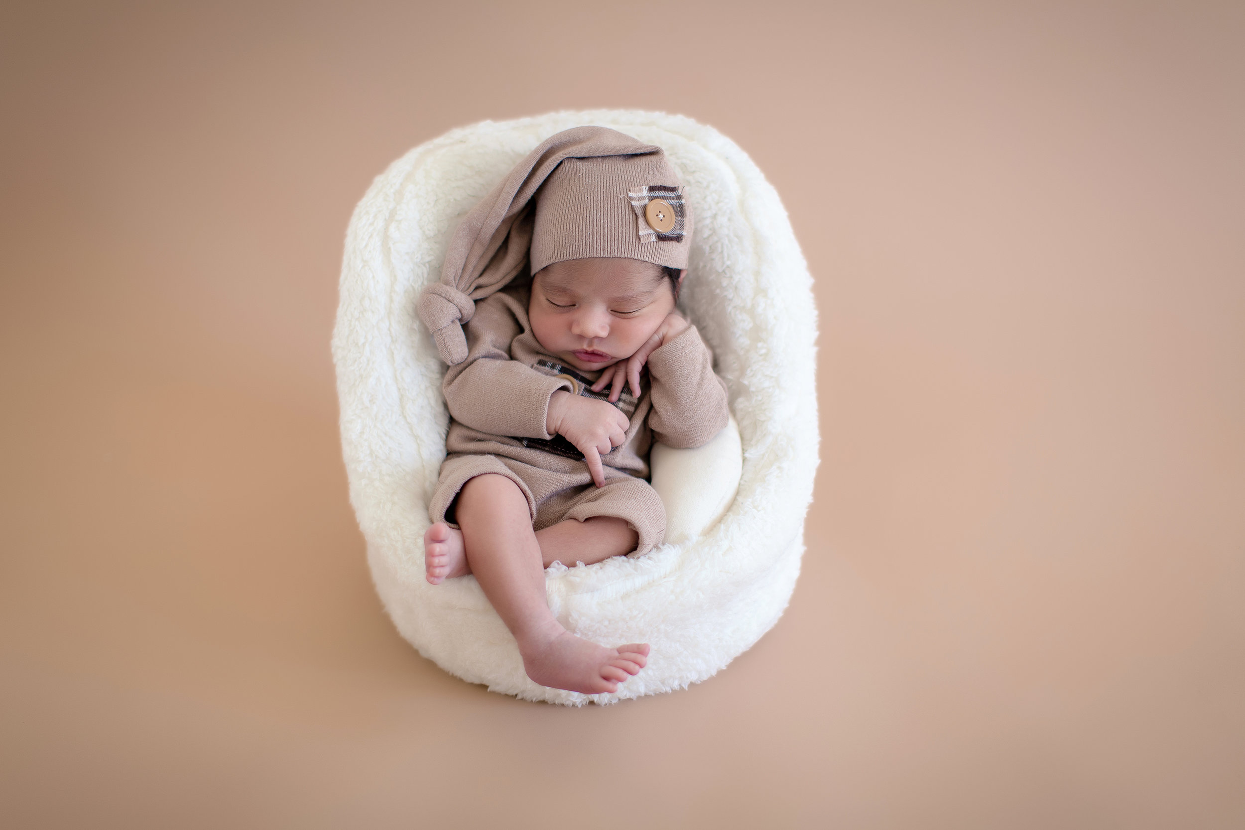 Newborn baby boy is posed comfortably in a little chair. Newborn Photoshoot ideas. Calgary baby and newborn photographer - Milashka Photography