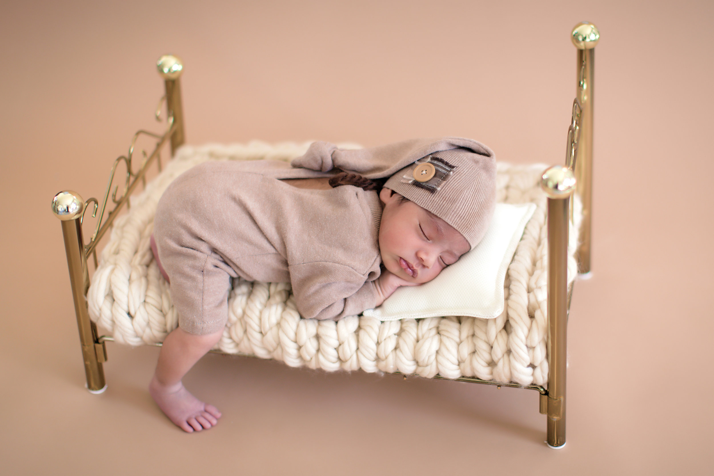 Newborn baby boy sleeping soundly on a little bed. Newborn baby photoshoot ideas - Calgary and Airdrie newborn and baby photographer