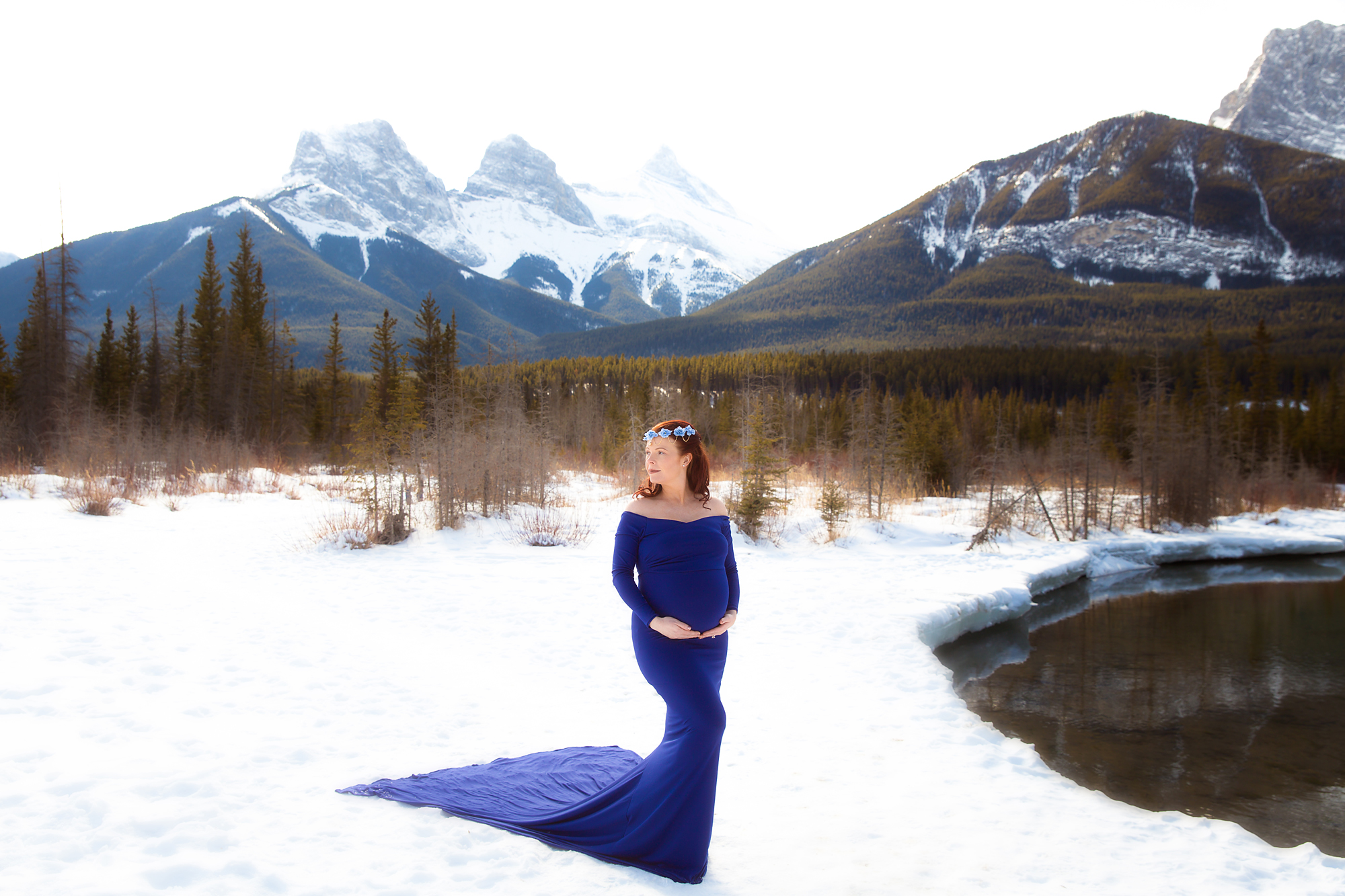Beautiful mother-to-be in a gorgeous royal blue gown standing in front of The Three Sister mountains in Canmore, Alberta, Canada during winter. Calgary, Airdrie, Canmore, Banff and Kananaskis Maternity Photographer - Milashka photography