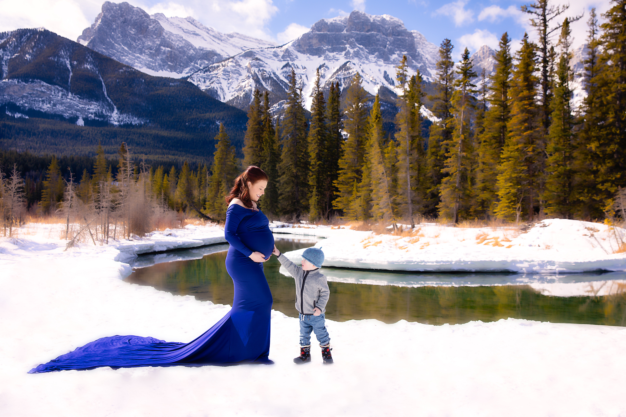 A little boy is touching his expecting mother's belly.  Mountain maternity session. Mom-to-be is wearing a beautiful royal blue gown and is standing on the snow in front of mountains and forest. Calgary Maternity photographer - Milashka Photography