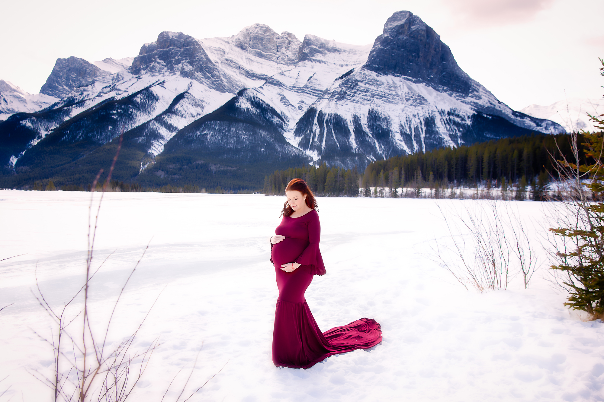 Mountain Maternity session in Canmore, Alberta, Canada. Mom-to-be is standing in front of Rocky Mountains on a snow, wearing a beautiful red gown. Calgary and Airdrie, Alberta maternity photographer - Milashka Photography