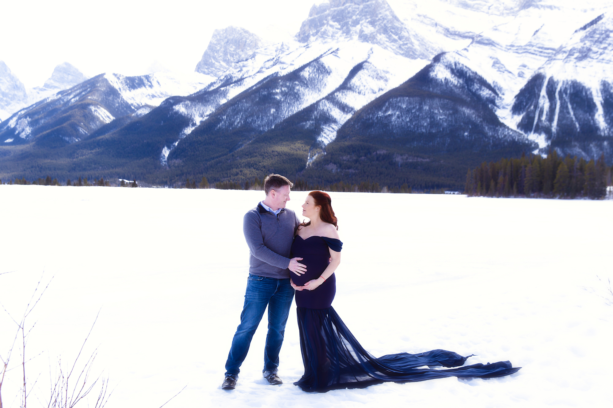 Mom and Dad to be standing on a snow in front of Rocky Mountains. Mom-to-be is wearing a gorgeous blue gown. Mountain Maternity Session in Kananaskis Country. Milashka Photography