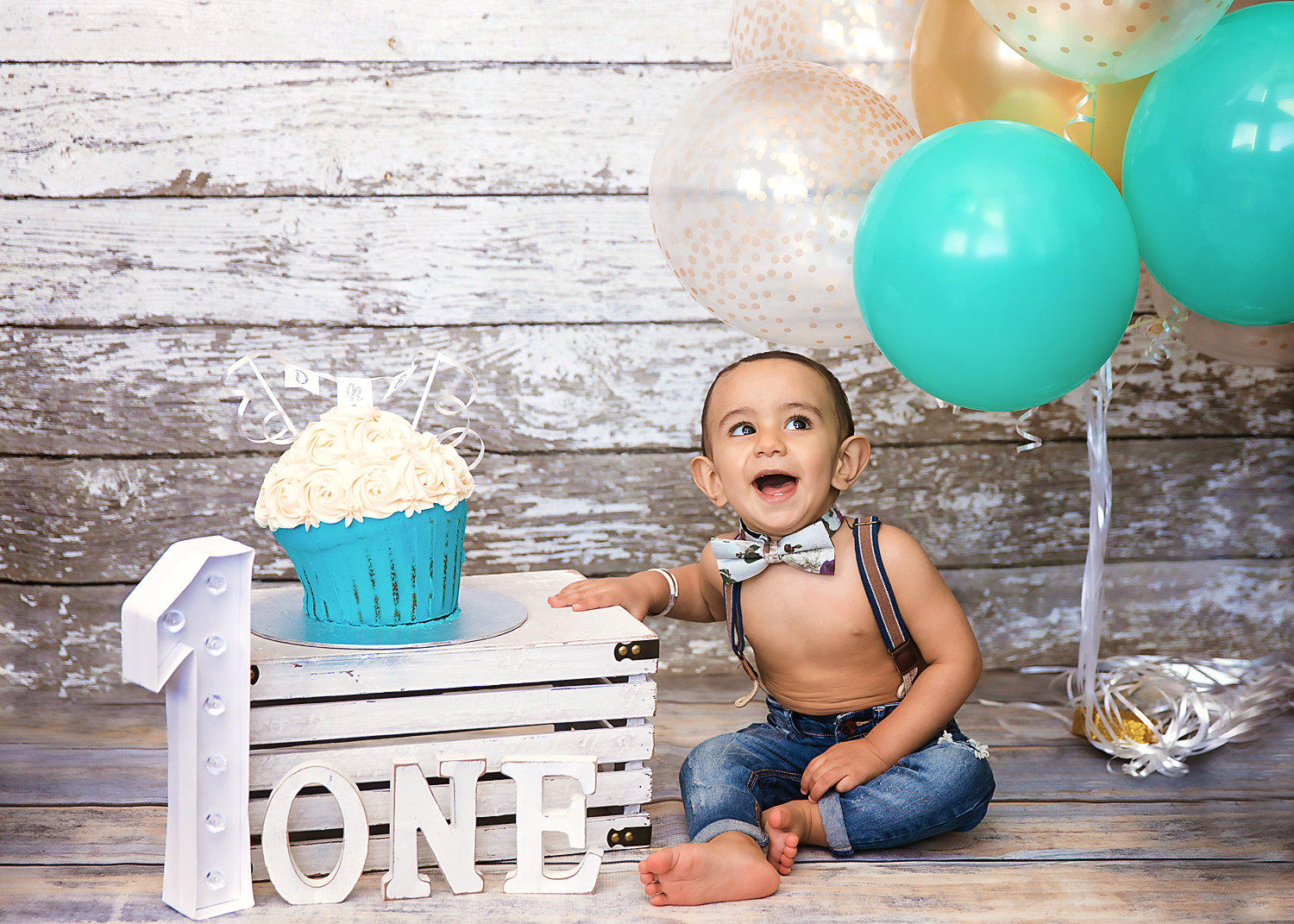 Cakesmash photoshoot idea. Little baby boy is sitting beside his cake and smiling. Calgary cakesmash photographer