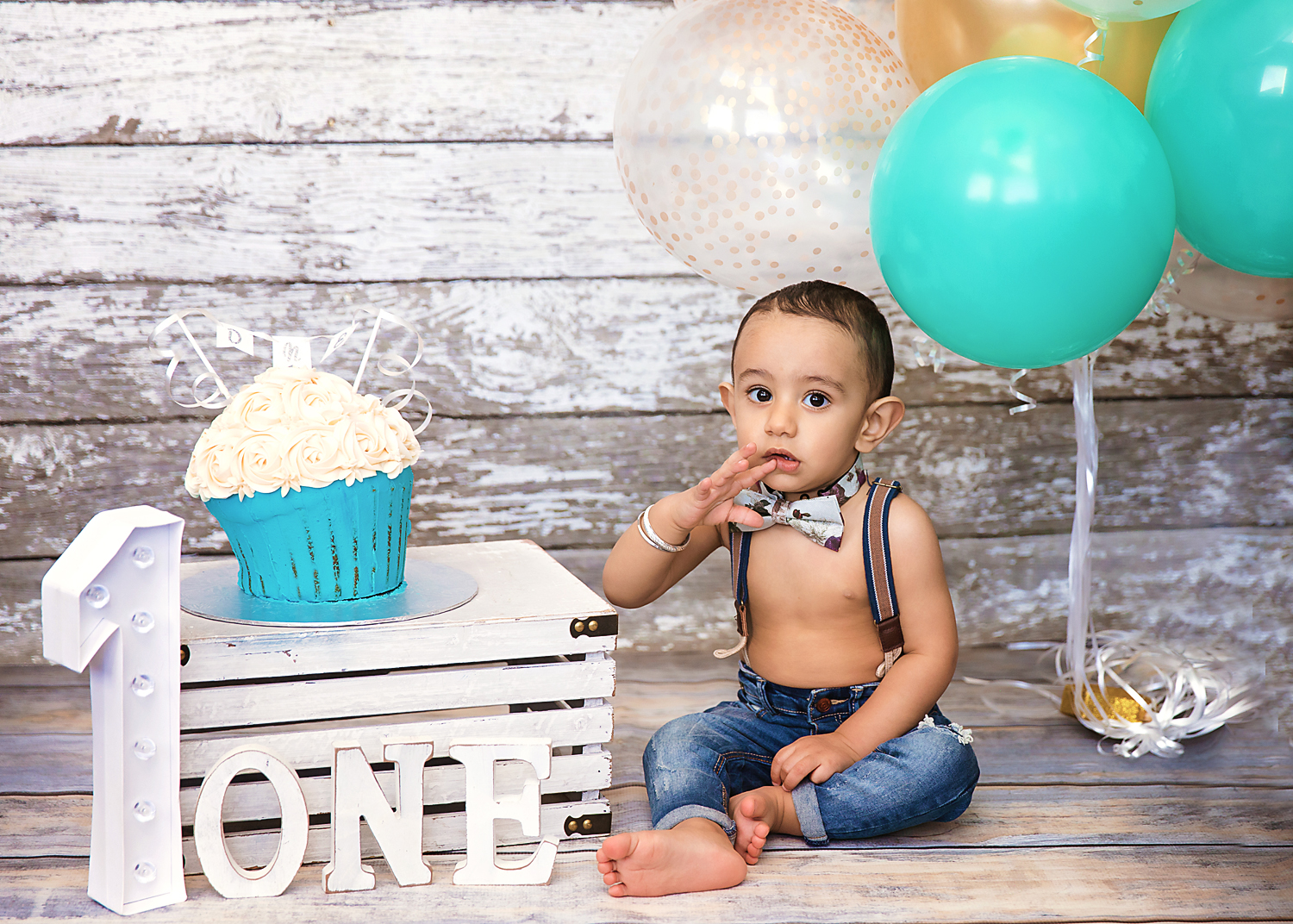 Cakesmash photoshoot. Baby boy is looking at the camera - not too sure what to do with his cake. Cakesmash set up. Calgary and Airdrie Cakesmash photographer