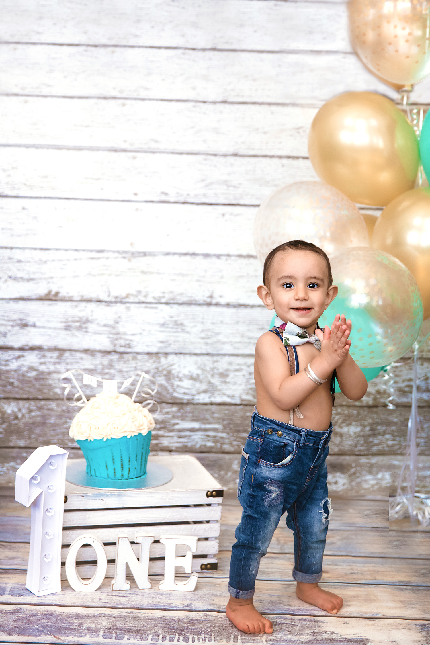 Birthday boy is standing proudly beside his birthday cake. First birthday photoshoot in Calgary, Alberta