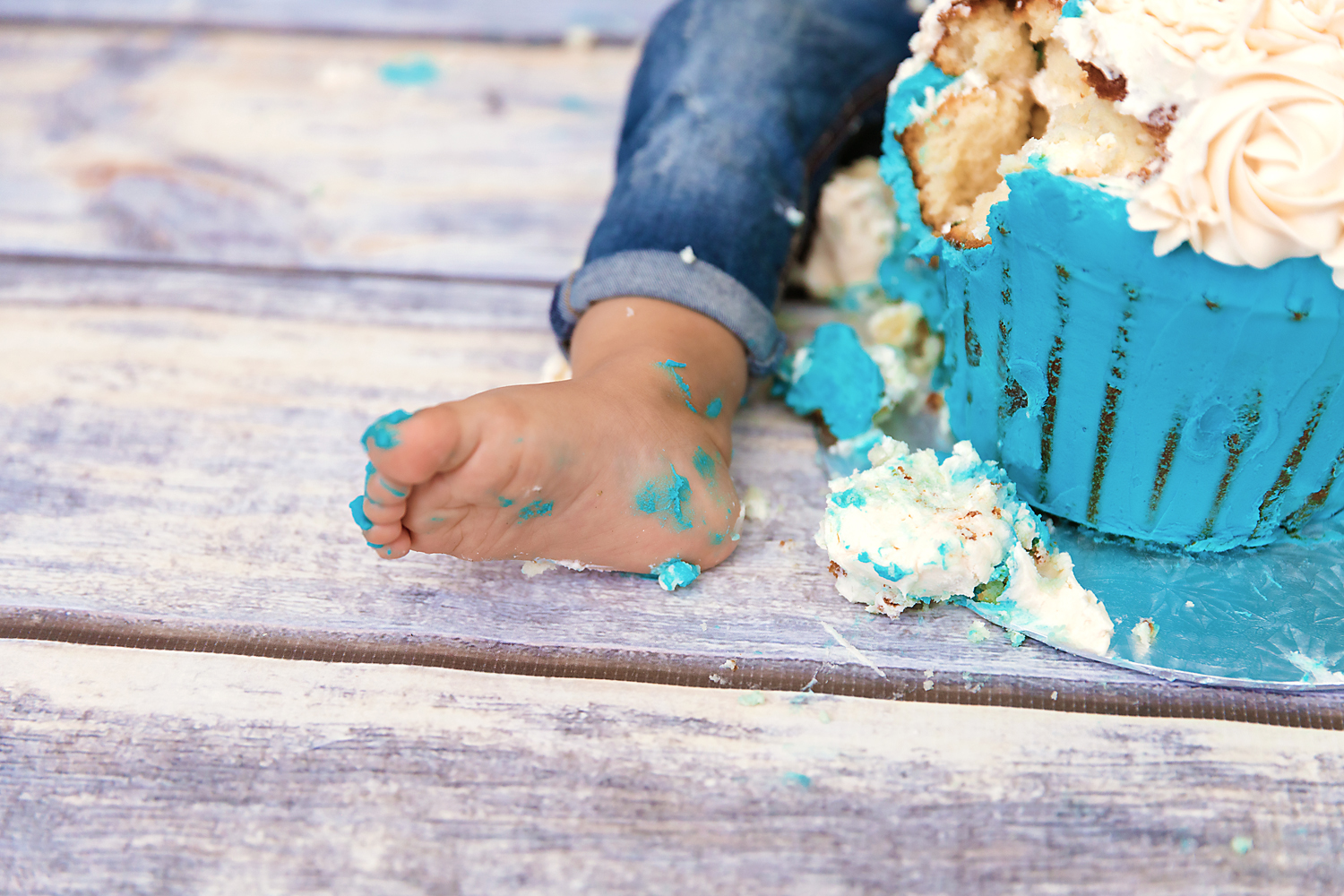 Little foot covered in a birthday cake icing. First birthday photoshoot. Cakesmash in Calgary, Alberta