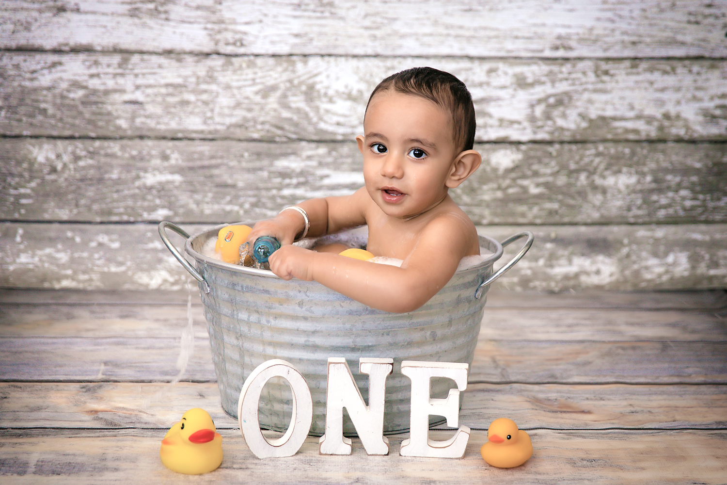 A little boy sitting in a tub and playing with rubber ducks. Smash and Splash photoshoot in Calgary, Alberta, Canada.