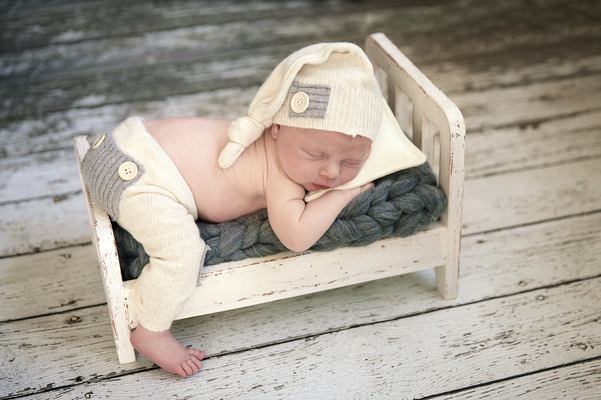 Baby boy is sleeping on an antique wooden bed. Newborn Photoshoot ideas. Calgary and area newborn photographer