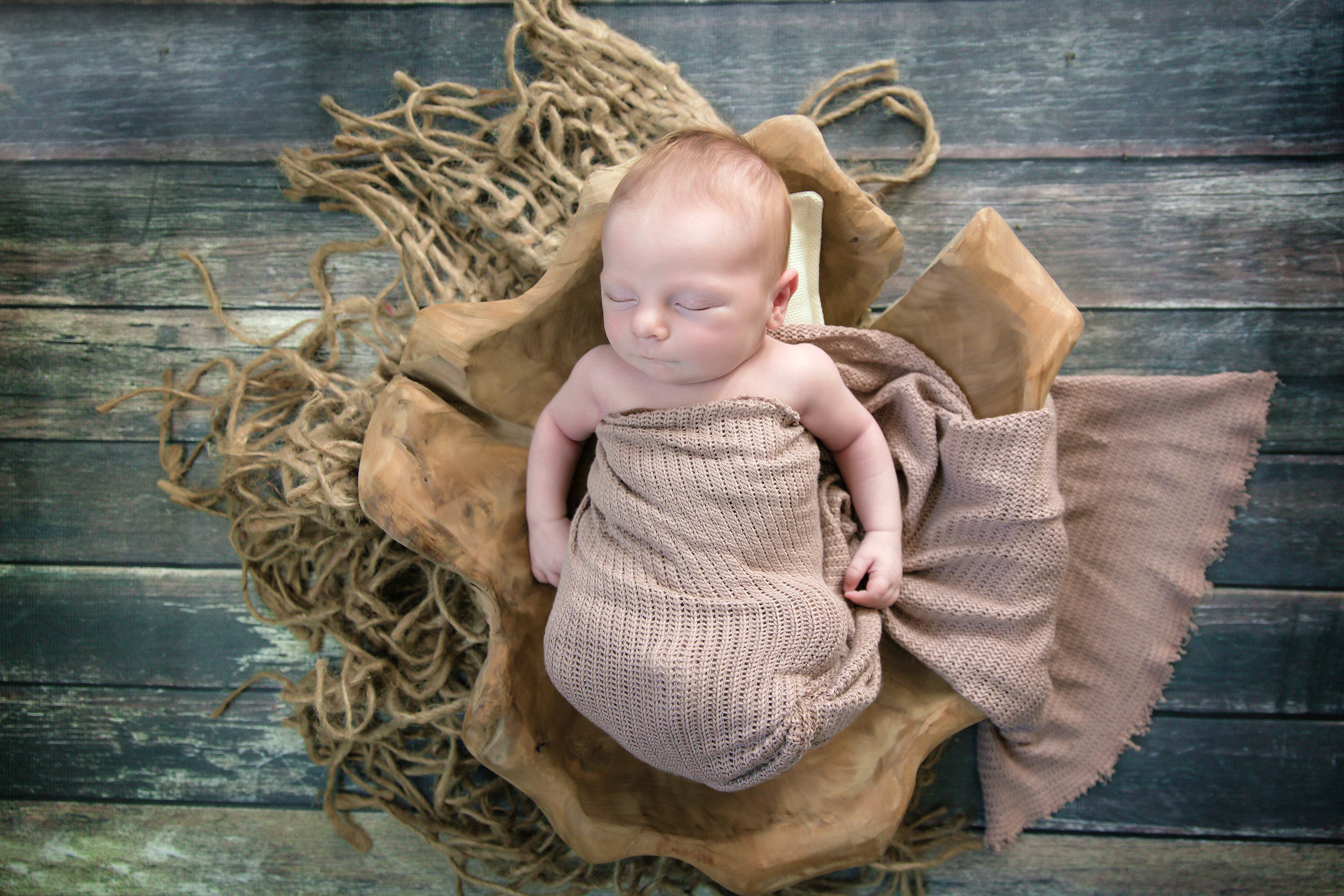 Baby boy is posed in a wooden bowl. Newborn photography. Calgary and Airdrie photographer