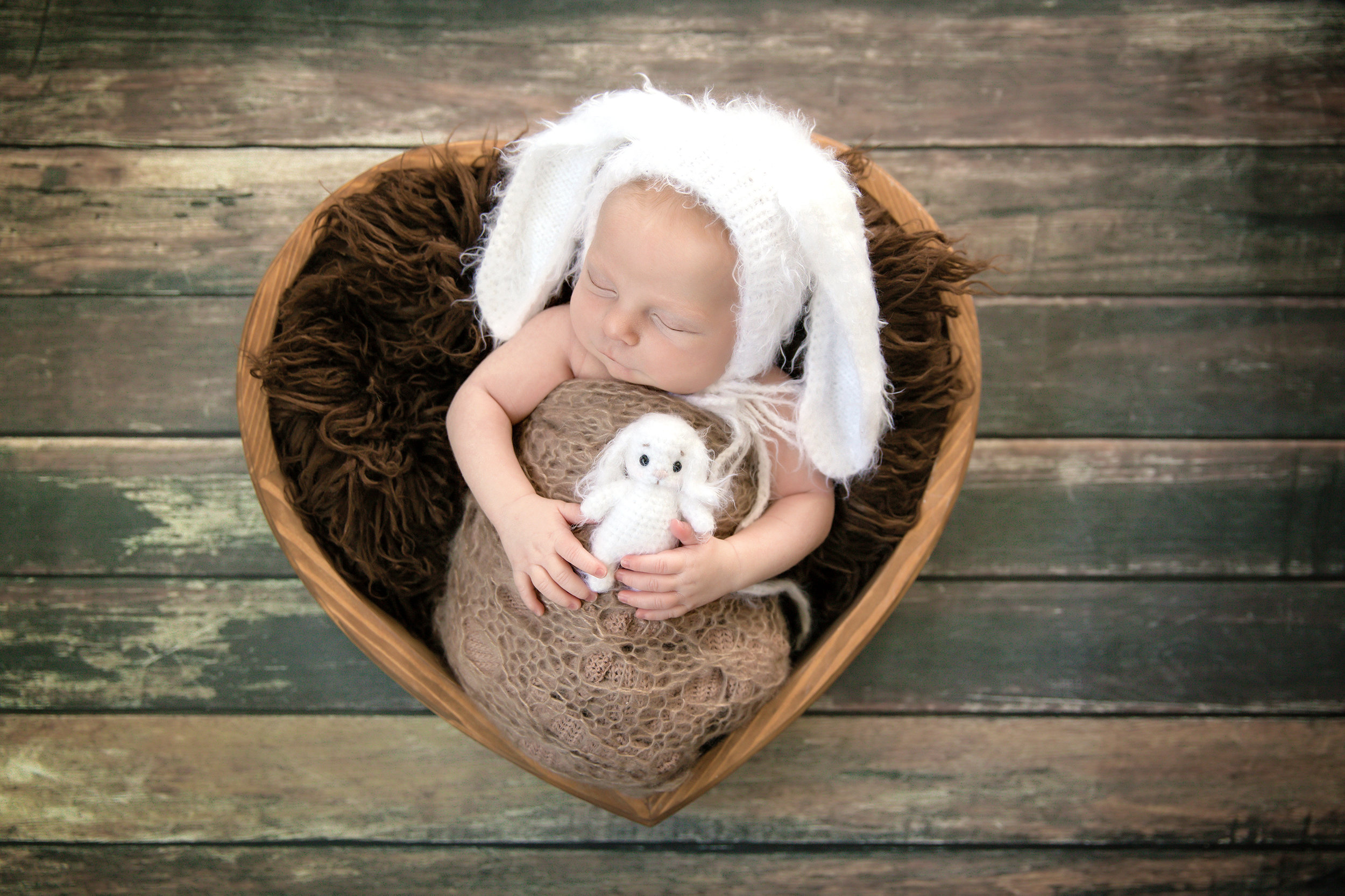 Baby boy is wearing a bunny hat and is holding a bunny toy posed in a heart bowl. Newborn photography by Milashka Photography. Calgary and Airdrie, Alberta photographer
