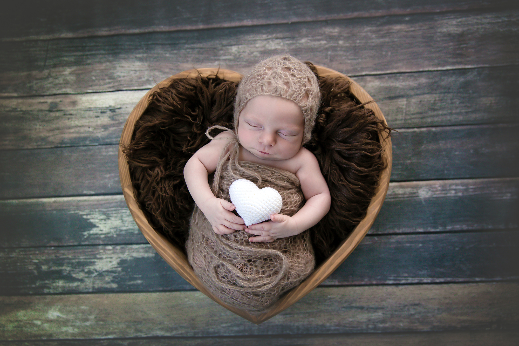 Baby boy is posed in a cute heart bowl and is holding a heart in his hands. Newborn photography by Milashka Photography. Calgary and Airdrie newborn and baby photographer
