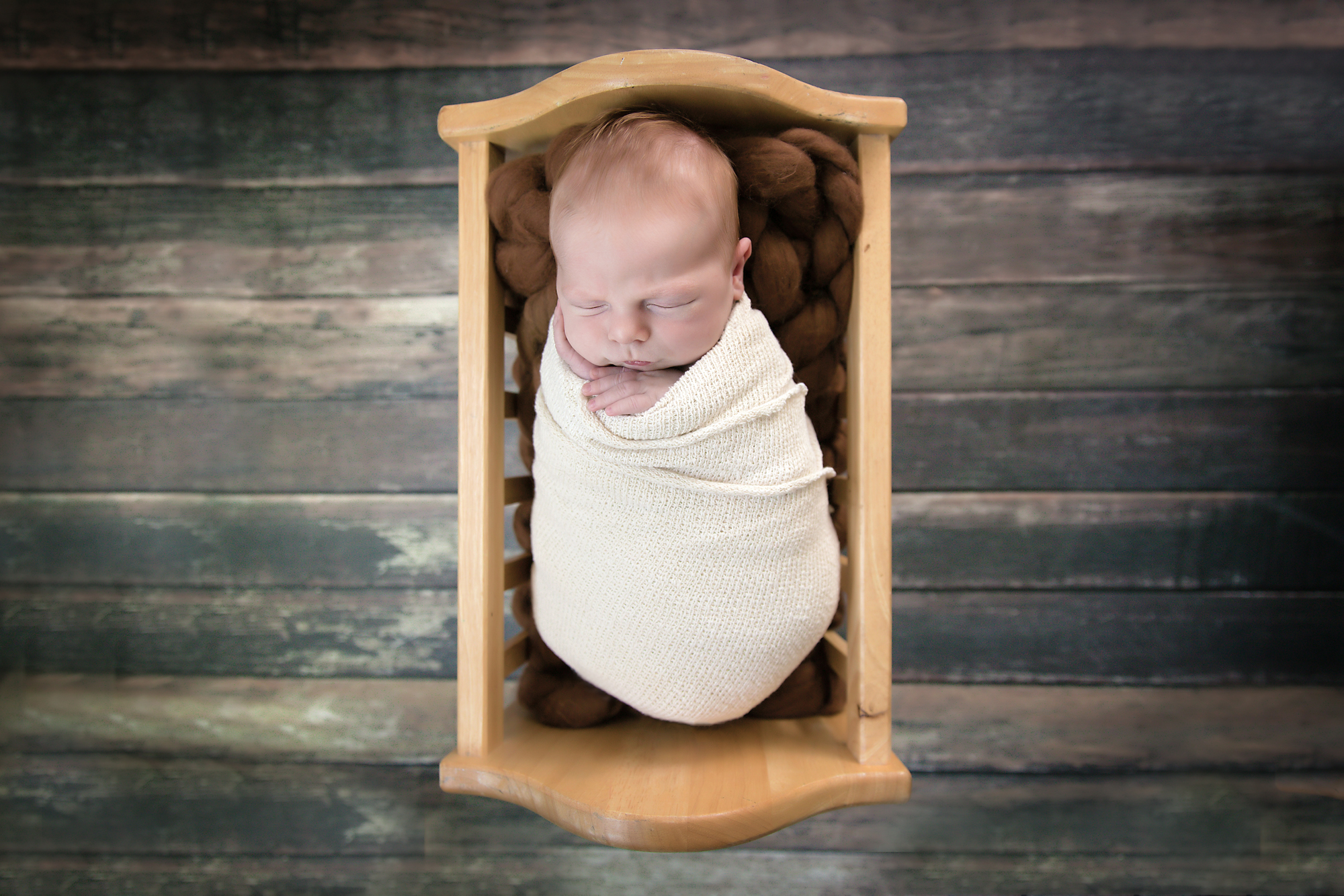 Newborn baby boy is sleeping soundly in a wooden crib. Newborn and Baby photoshoot ideas. Calgary and Airdrie, Alberta Newborn Photographer - Milashka Photography
