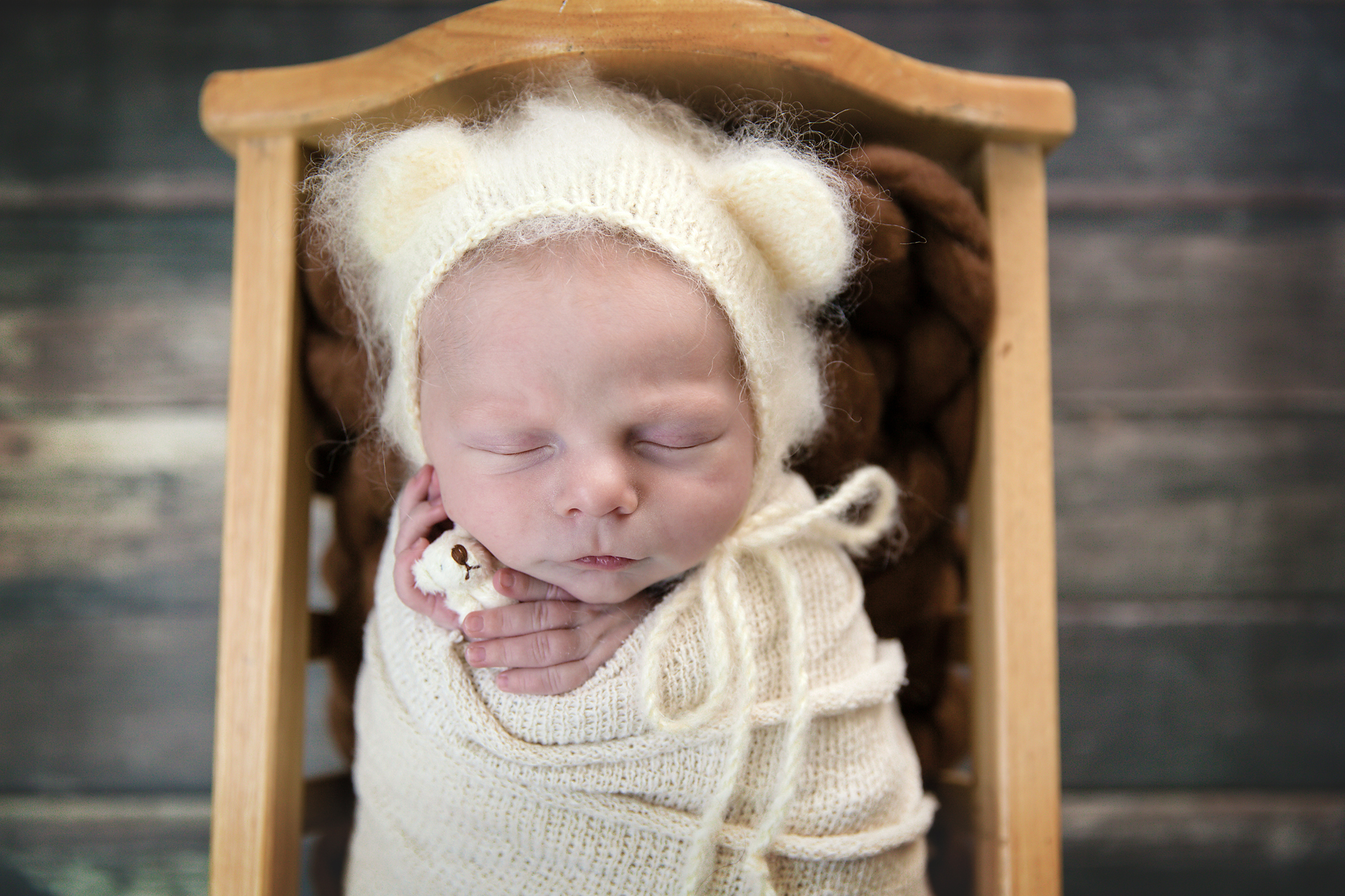 Newborn baby boy is wearing a bear hat and is holding a little tiny bear toy in his hands. Calgary newborn and baby photographer - Milashka Photography