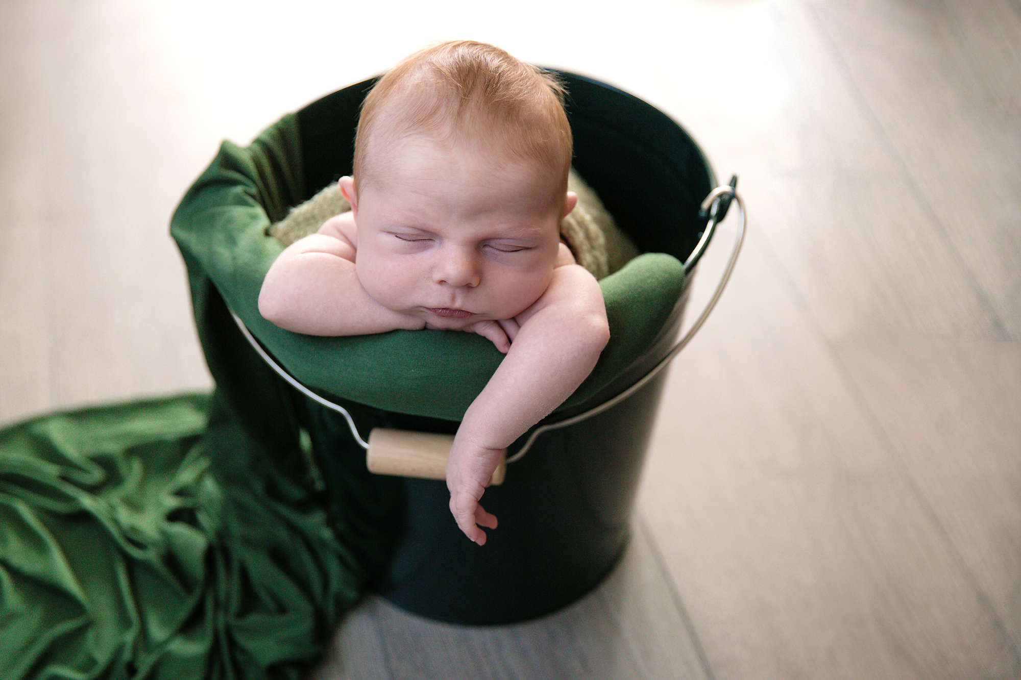 Baby boy in a bucket with his little arm hanging. Baby boy born on St. Patricks day - green bucket and green wrap. Newborn Photoshoot ideas. Baby born on St. Patrick's day ideas. Calgary Newborn Photographer