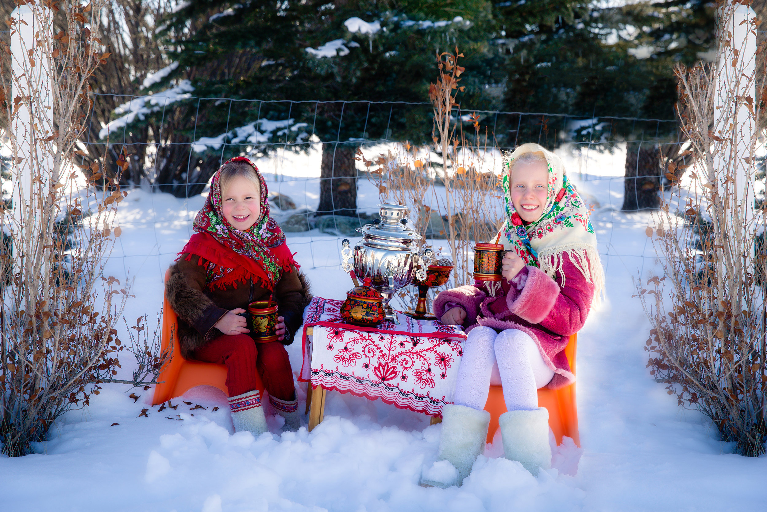 "Two sisters are dressed in Russian traditional clothes, drinking tea from Russian traditional dishes and Samovar and eating ""Pryaniki"" - Russian gingerbread cookies"