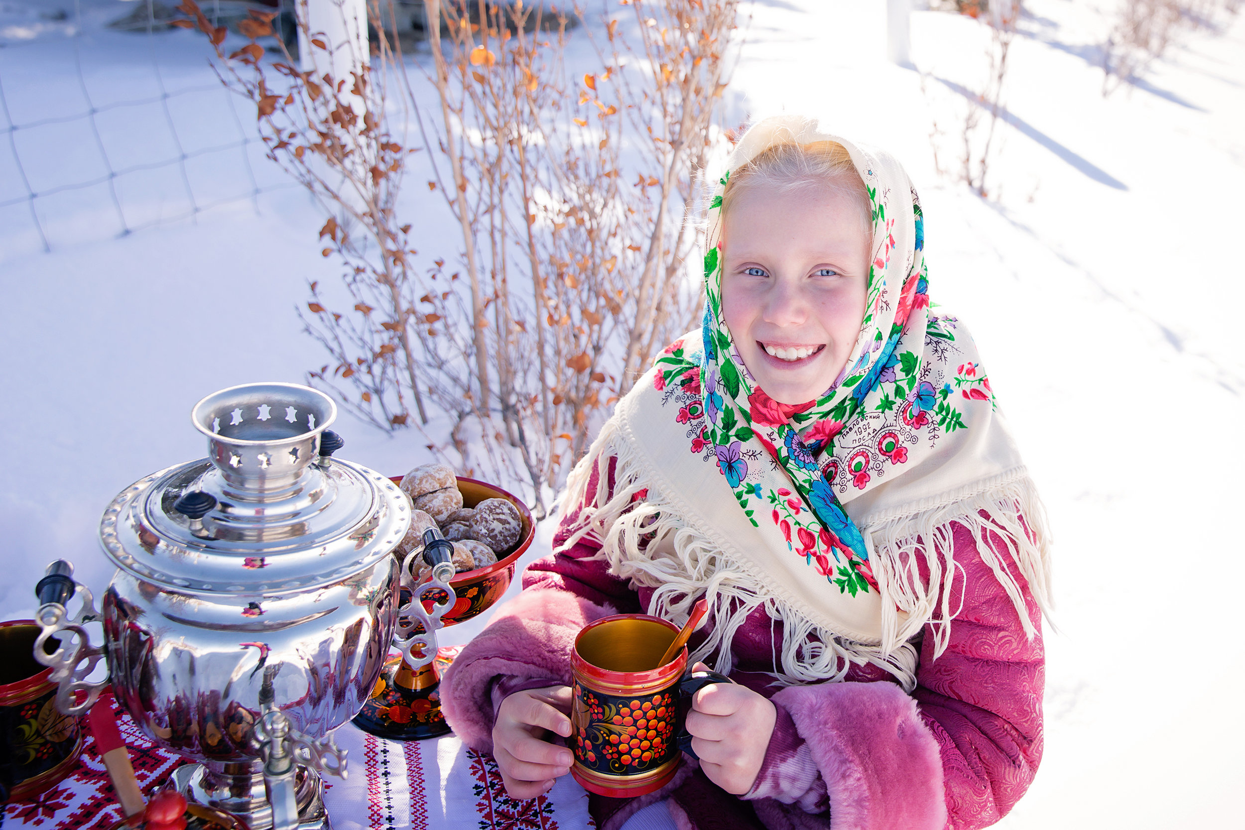 Russian inspired photoshoot. A girl is dressed in a traditional Russian clothes and drinking tea from a Samovar and Russian traditional dishes. Russian Calgary Photographer - Milashka Photography