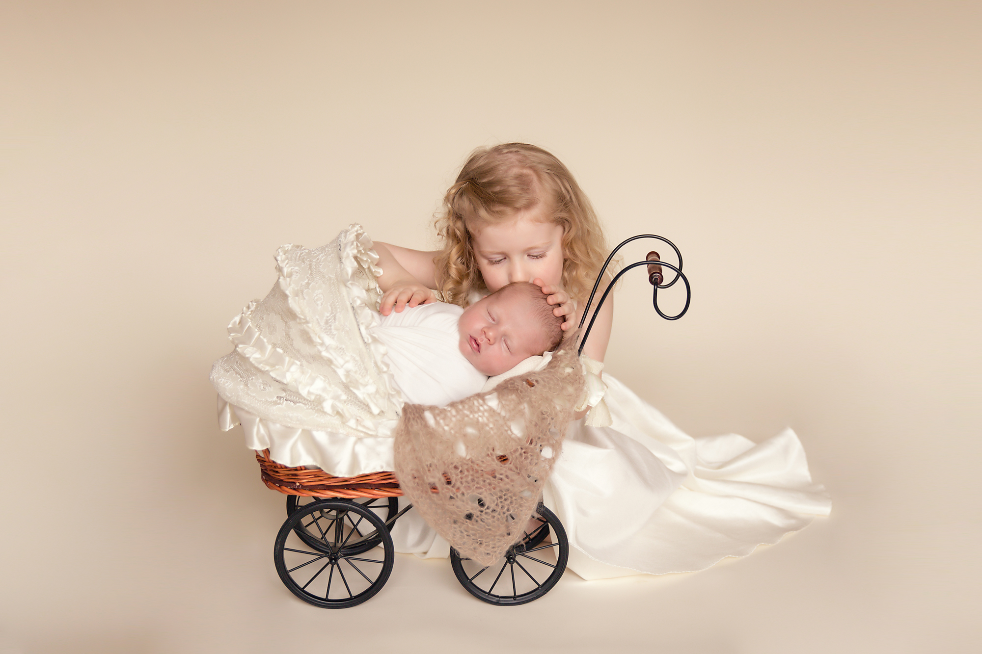 Big sister is kissing her newborn brother in a stroller. Calgary Newborn and Baby photographer - Milashka Photography.