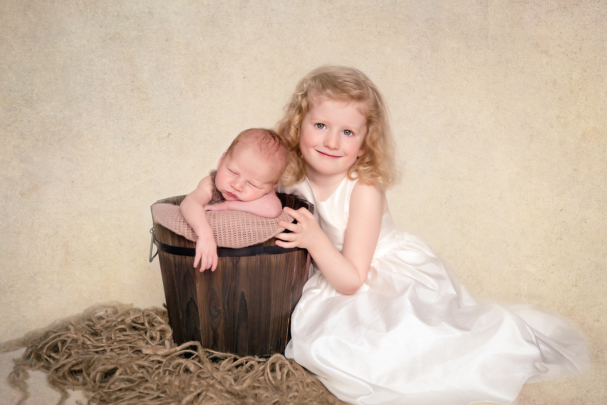 Big sister is sitting beside her baby brother in a bucket. Newborn photography. Calgary Newborn and Baby photographer - Milashka Photography.