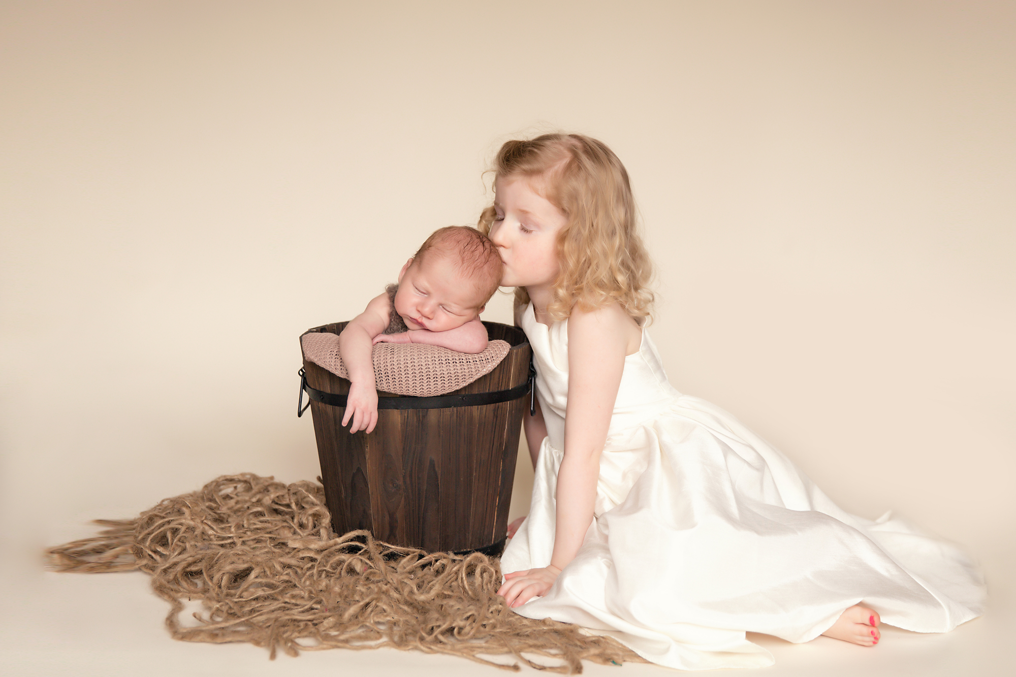 Big sister is kissing her little newborn baby brother in a bucket. Newborn photography. Calgary Newborn and Baby photographer - Milashka Photography.
