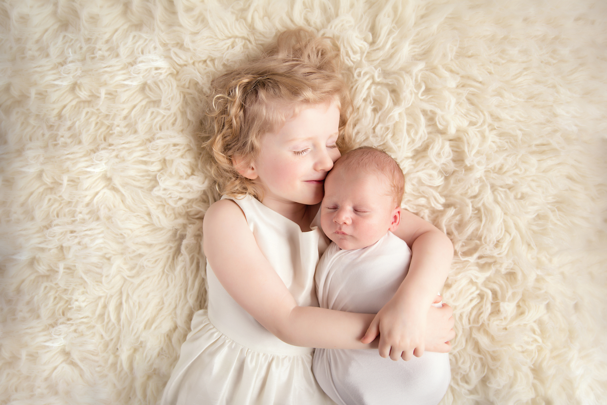 Big sister is giving her newborn baby brother a kiss. Newborn photography. Siblings on a flokati. Calgary Newborn and Baby photographer - Milashka Photography.