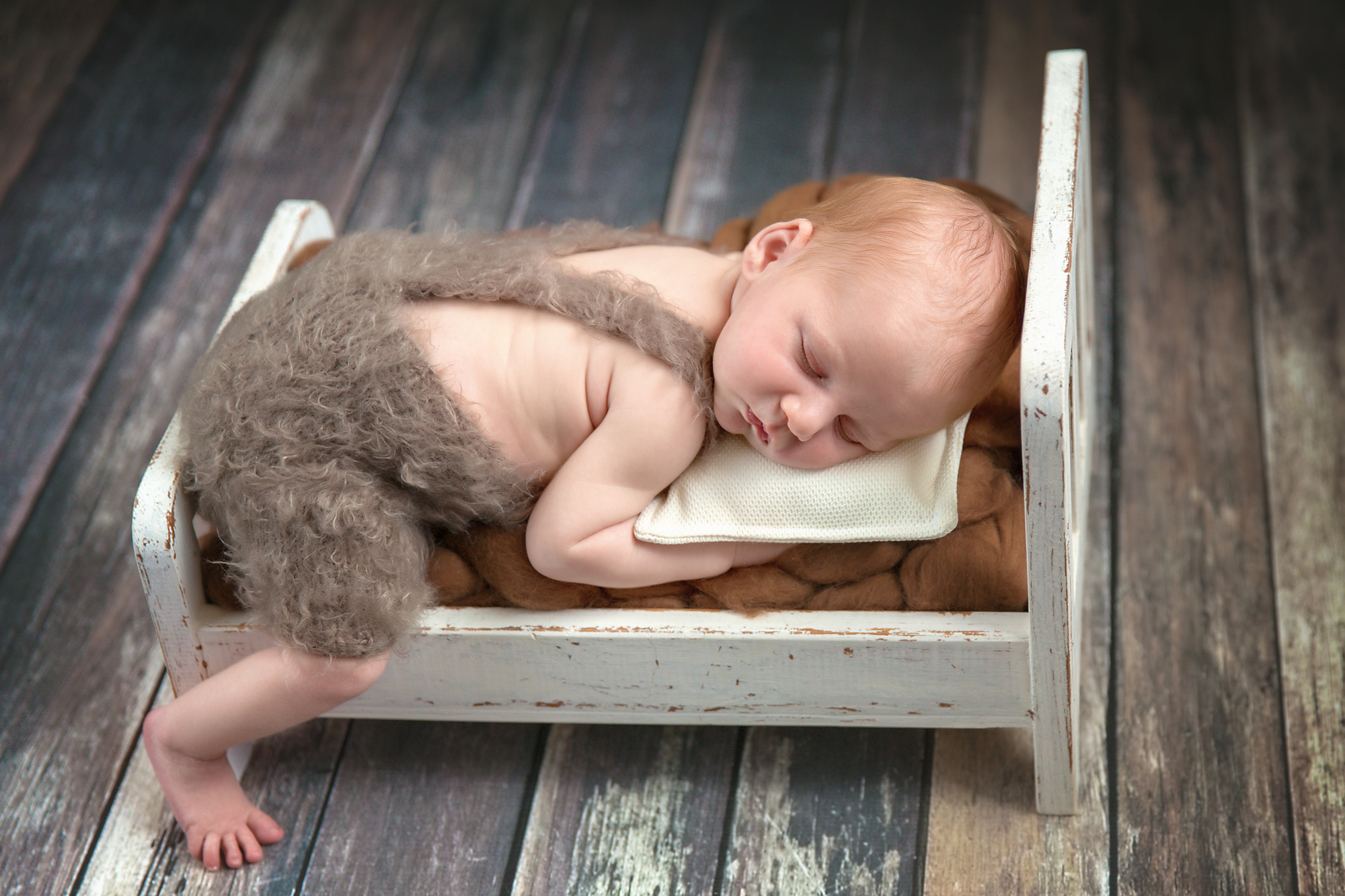 Baby boy is sleeping soundly on a little antique bed. Calgary Newborn and Baby photographer - Milashka Photography.