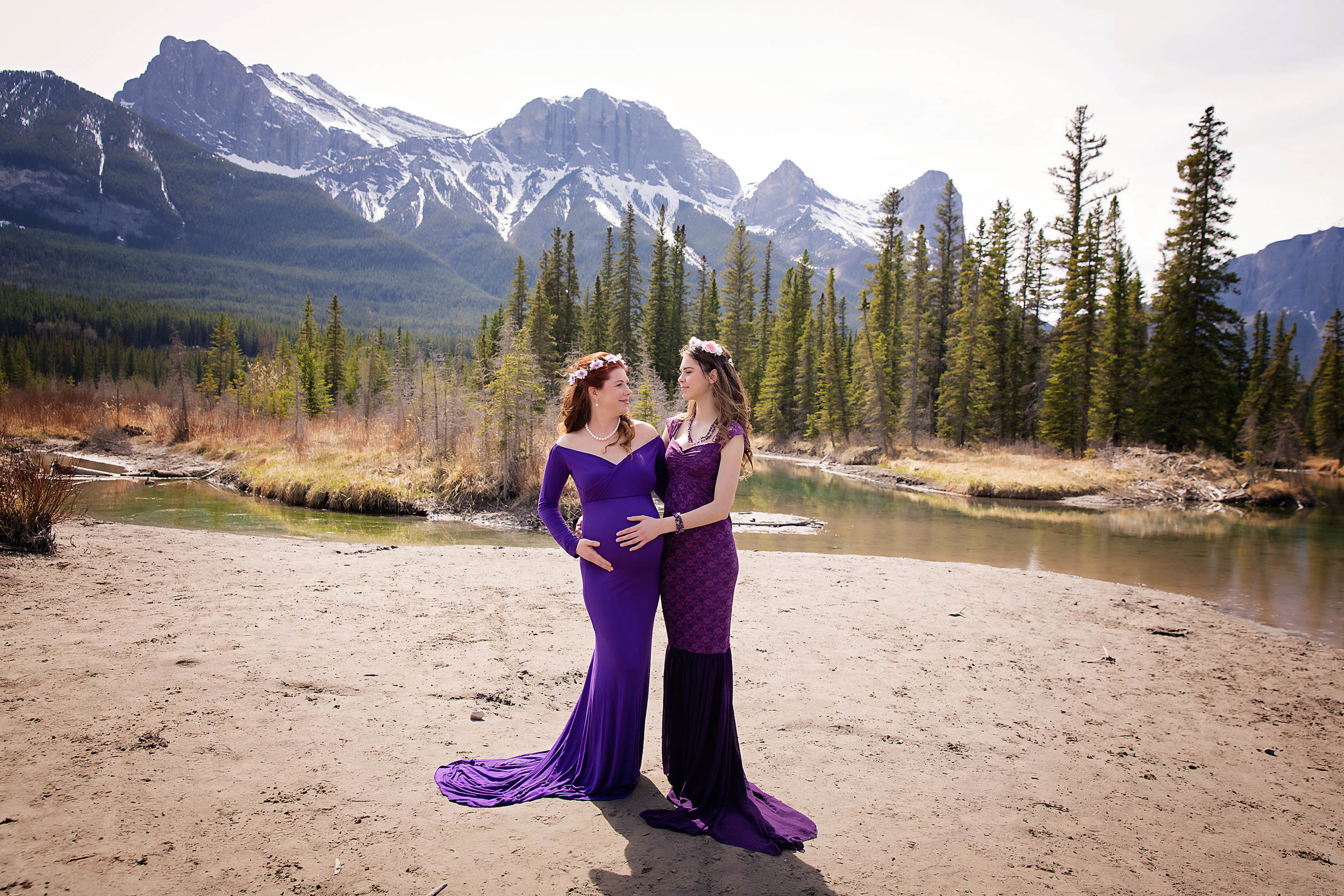 Mother and teenage daughter maternity shot. Both are wearing purple gowns and looking at each other.
