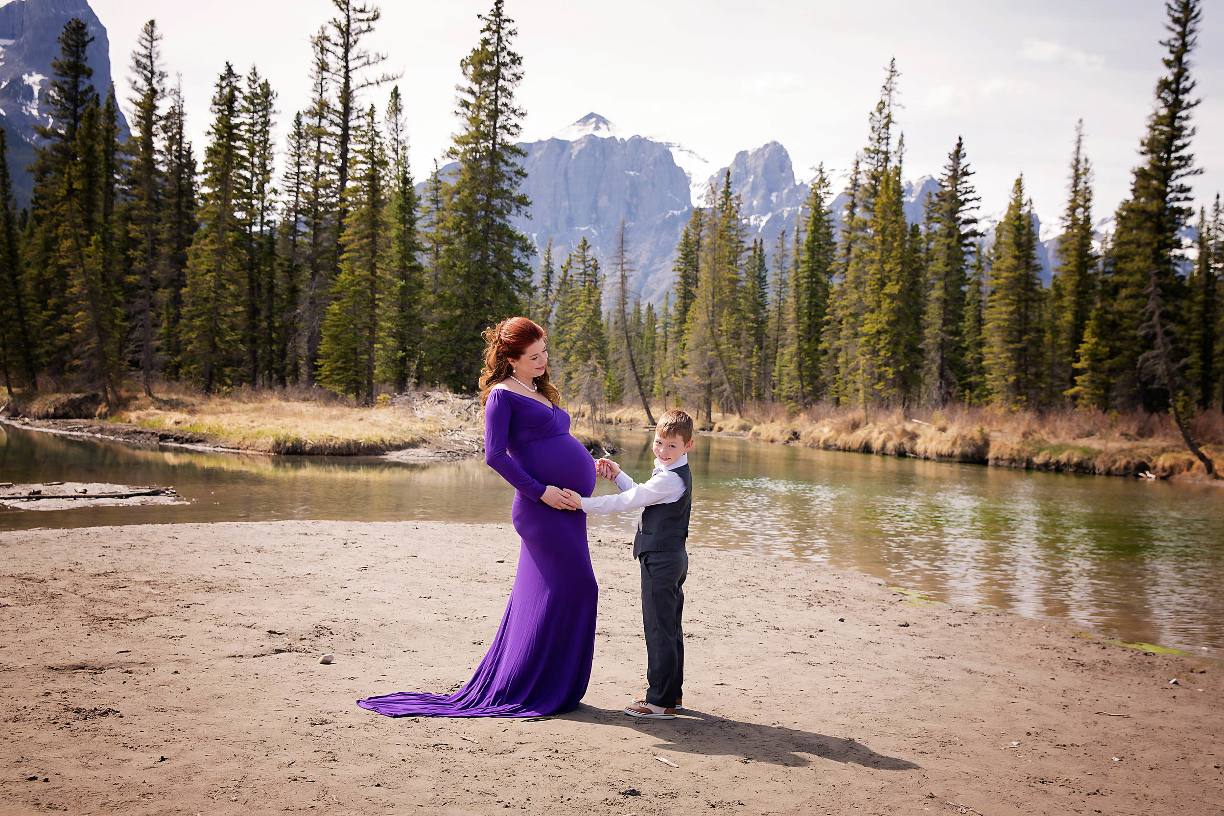 Mother and son maternity in the mountains shot. Mom to be is wearing a purple gown and looking at her son while a 7 year old boy is looking straight at the camera and smiling. Calgary maternity photographer - Milashka Photography