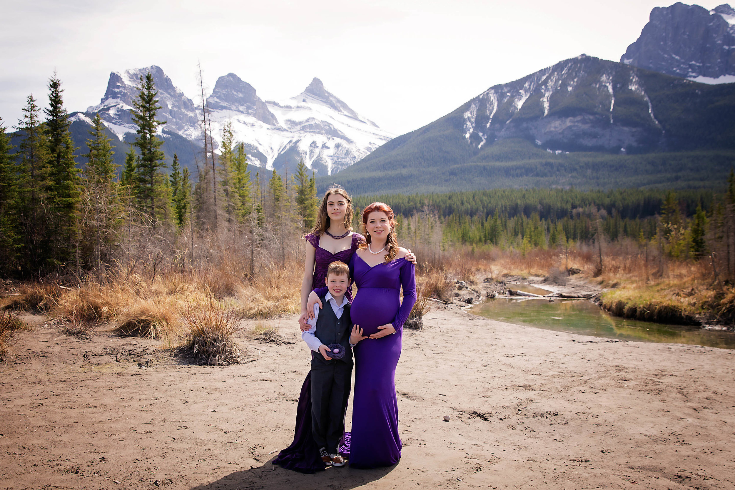 Third baby is on its way! Mom to be and her two children are posing for the camera in this maternity session. Mountain Maternity Session in Canmore, Alberta, Canada. Three sisters mountains. Calgary and Airdrie Newborn and Maternity Photographer - Milashka Photography