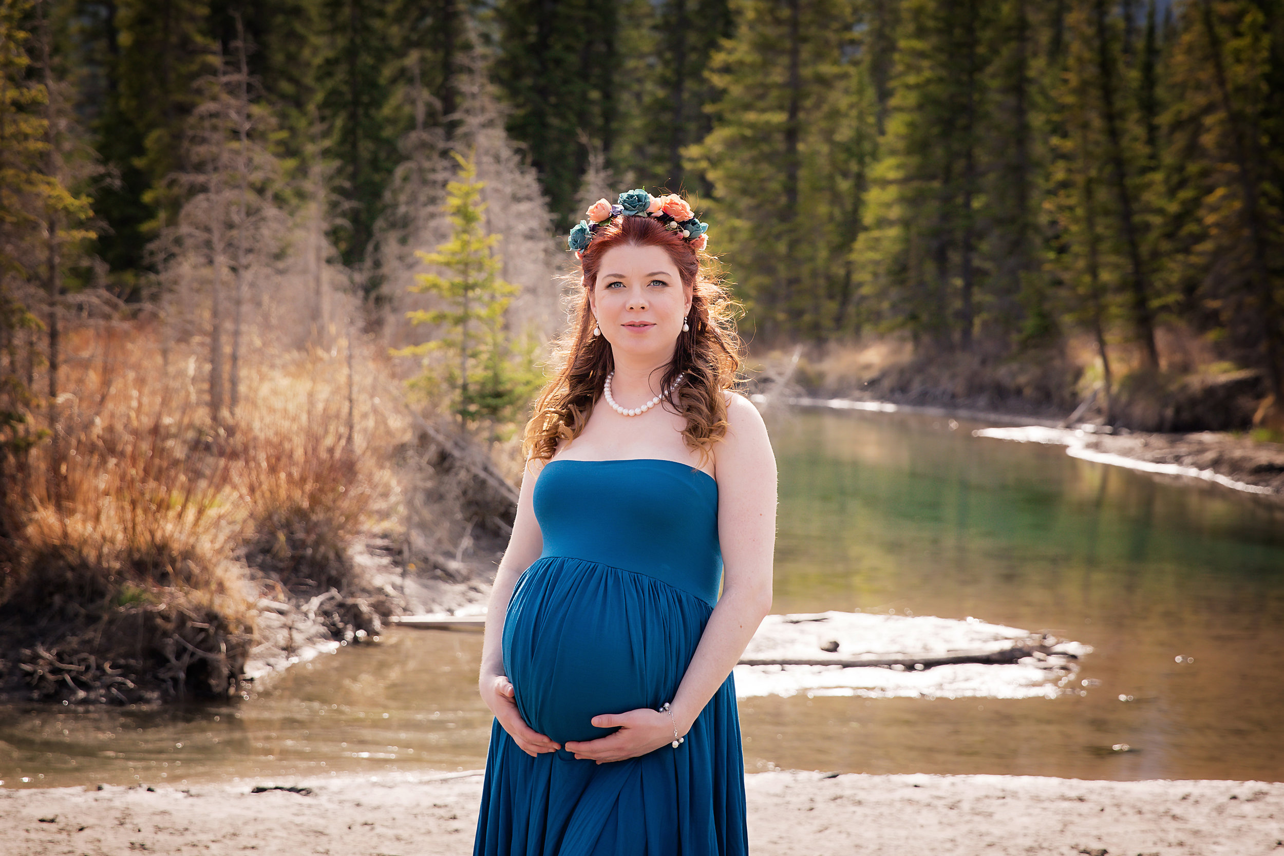 Mother - to - be is posing for the camera wearing a blue gown in-front of a river and trees in this mountain maternity session in Kananaskis country, Alberta, Canada.