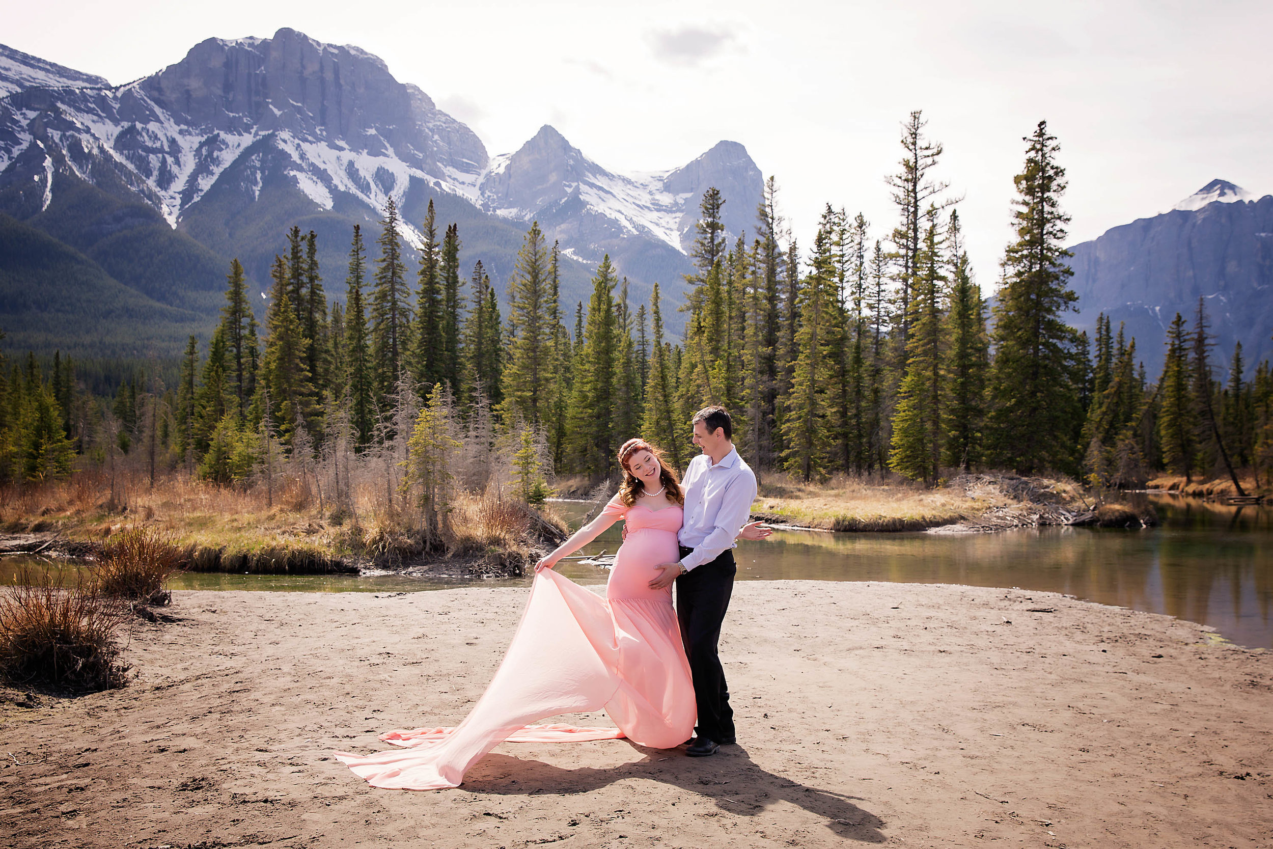 Parents to be are posing in this maternity mountain photoshoot. Mama is wearing a beautiful pink dress. Calgary, Alberta