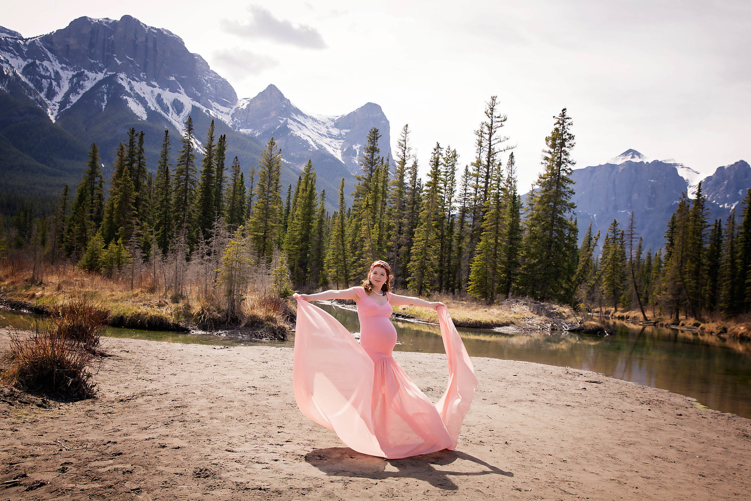 Pink dress. Mother to be is wearing a pink gown in this mountain maternity session. Calgary photographer.