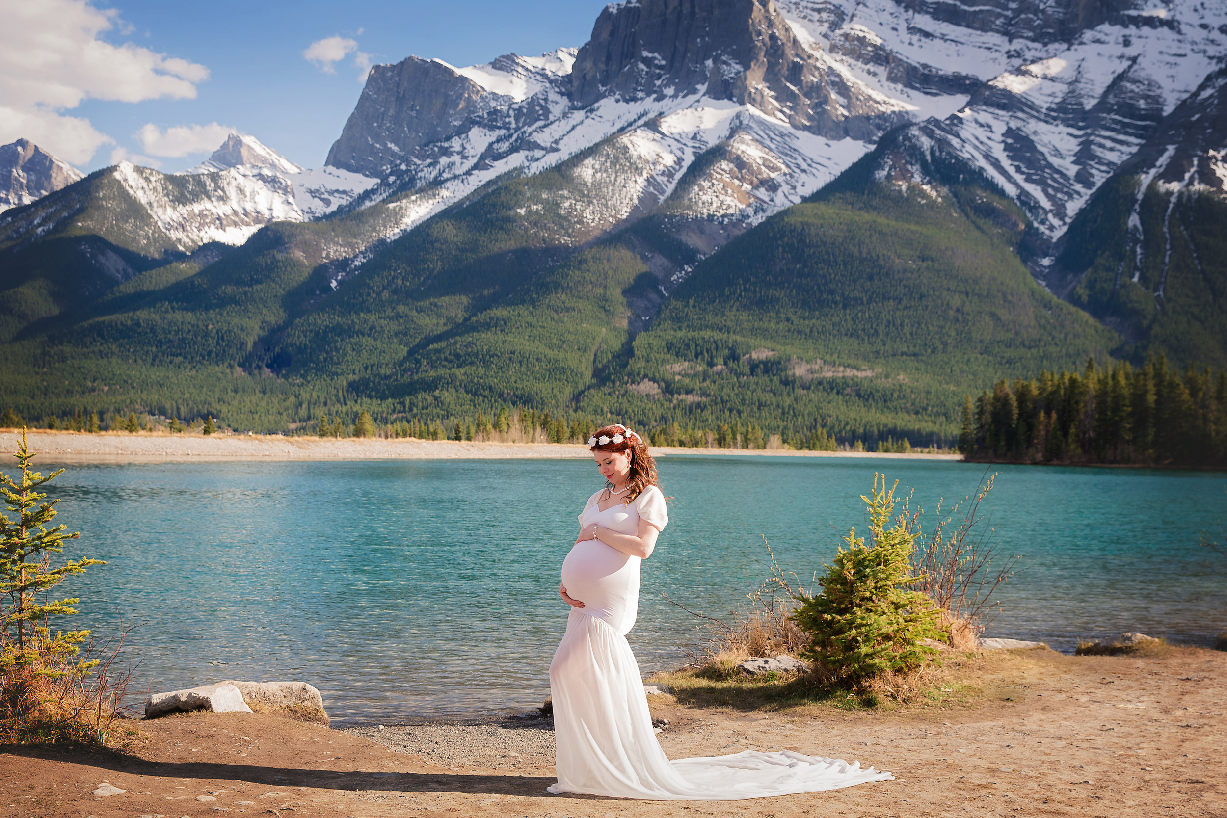 Beautiful mother-to-be is wearing a white dress in Canmore, Alberta, Canada. Calgary Maternity Photoshoot. Calgary and Airdrie maternity photographer - Milashka Photography
