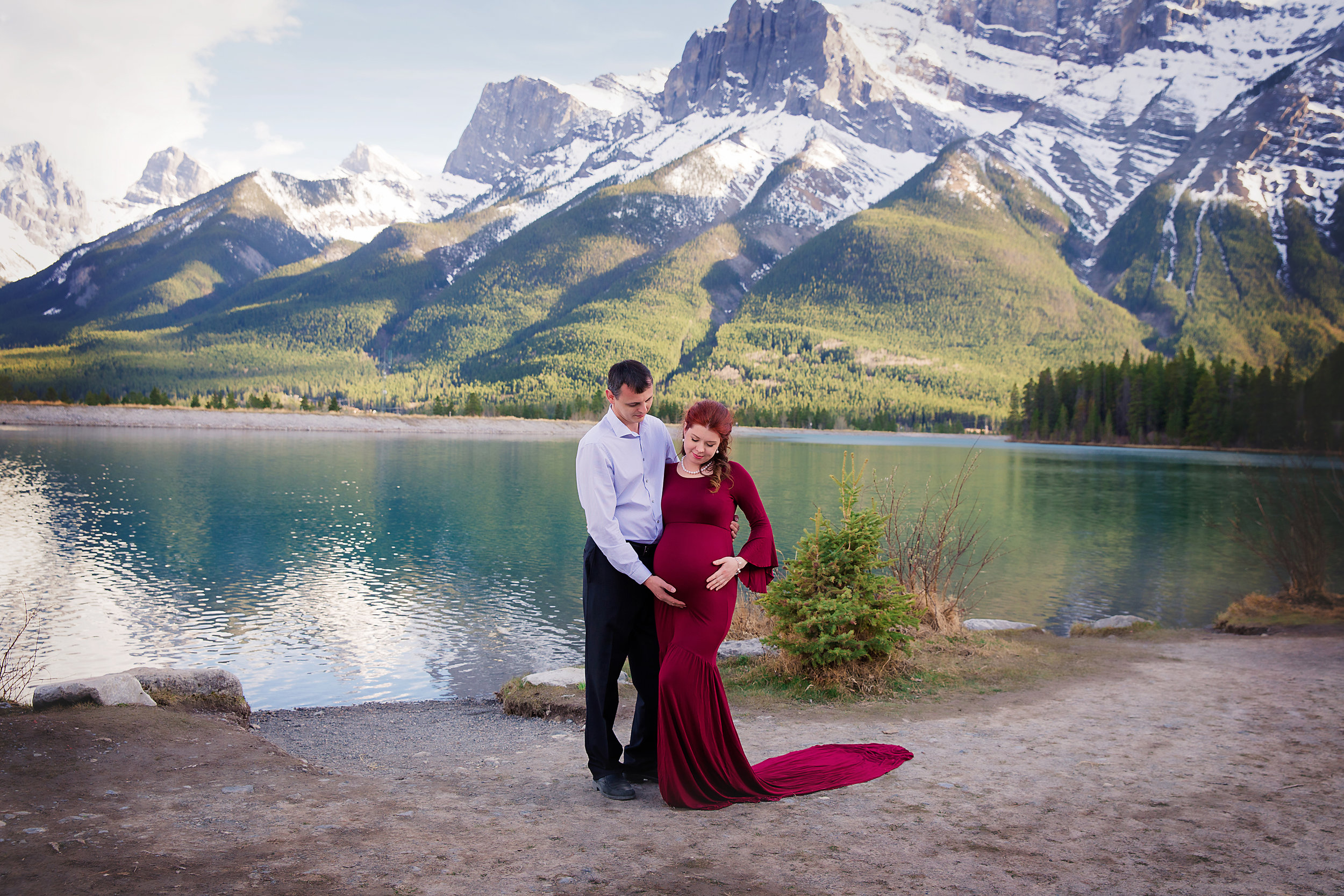 Parents to be in the mountain maternity session. Mama is wearing a red gown.