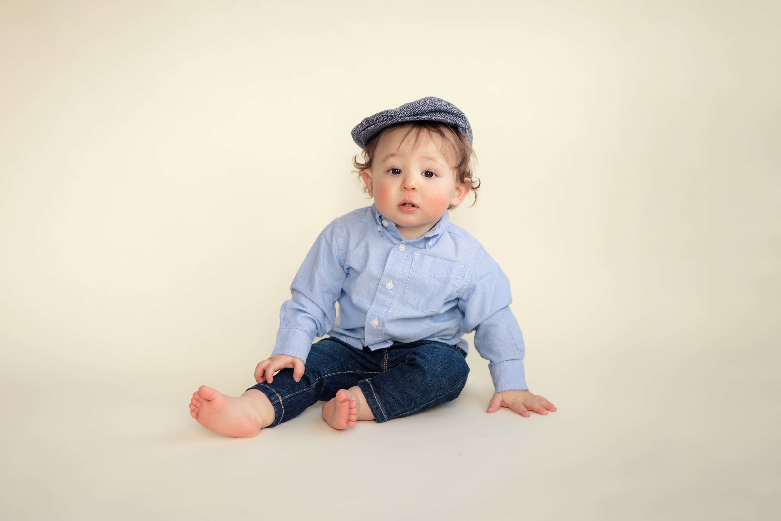 Baby boy is sitting on a seamless backdrop and is wearing a cute hat.