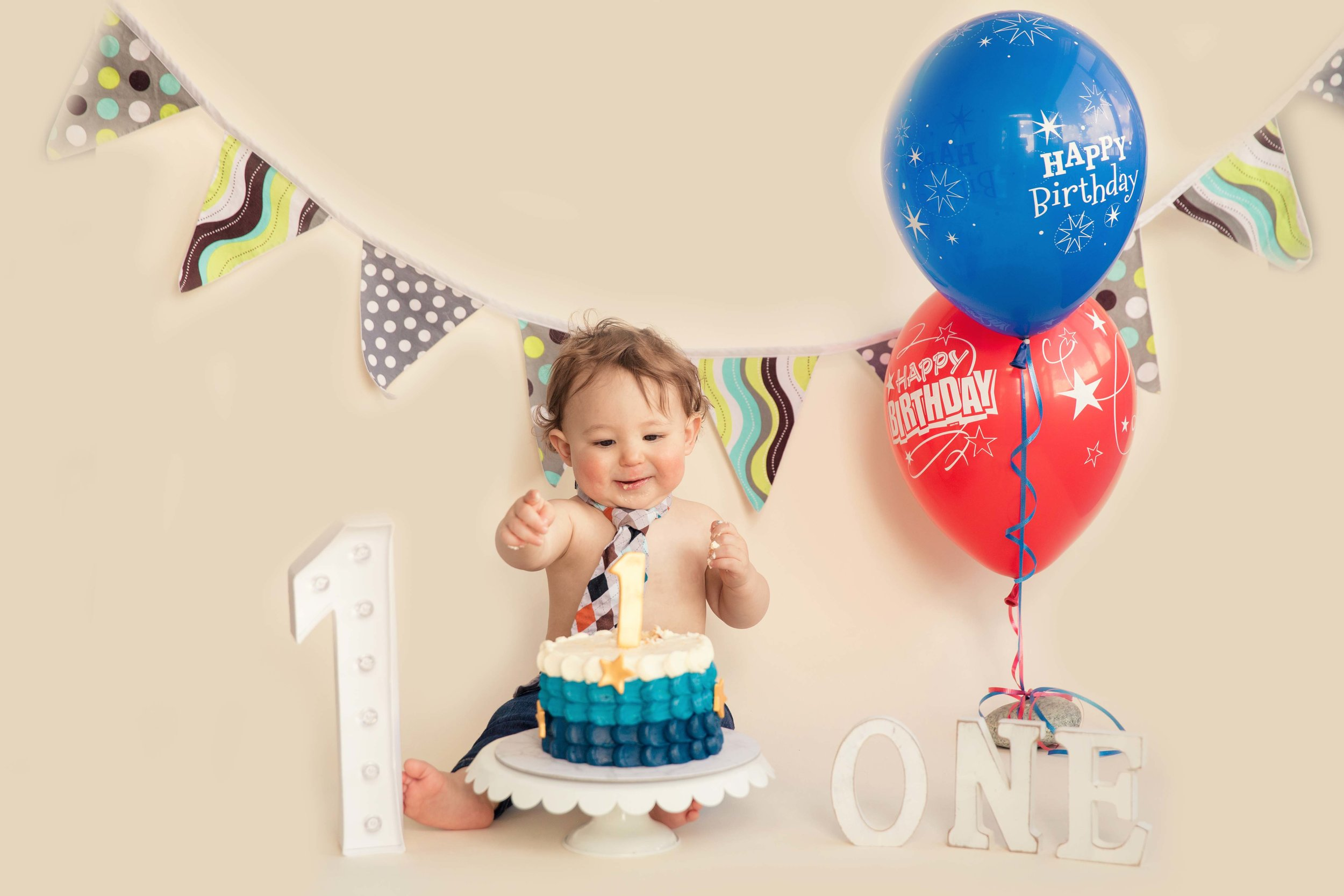 Baby boy is about to smash his 1st birthday cake. Calgary Cakesmash Photographer.