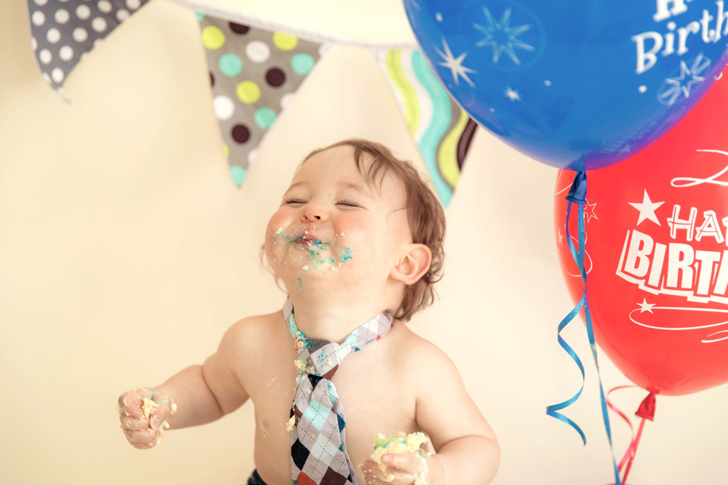 Happy little 1 year old is eating his first cake. Calgary and Airdrie cakesmash photographer