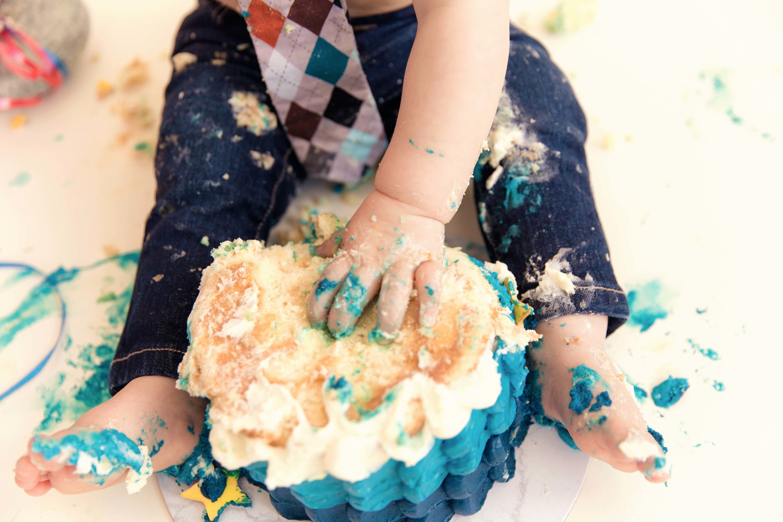 Little feet and a hand covered in a cake. Cakesmash action in Calgary, Alberta