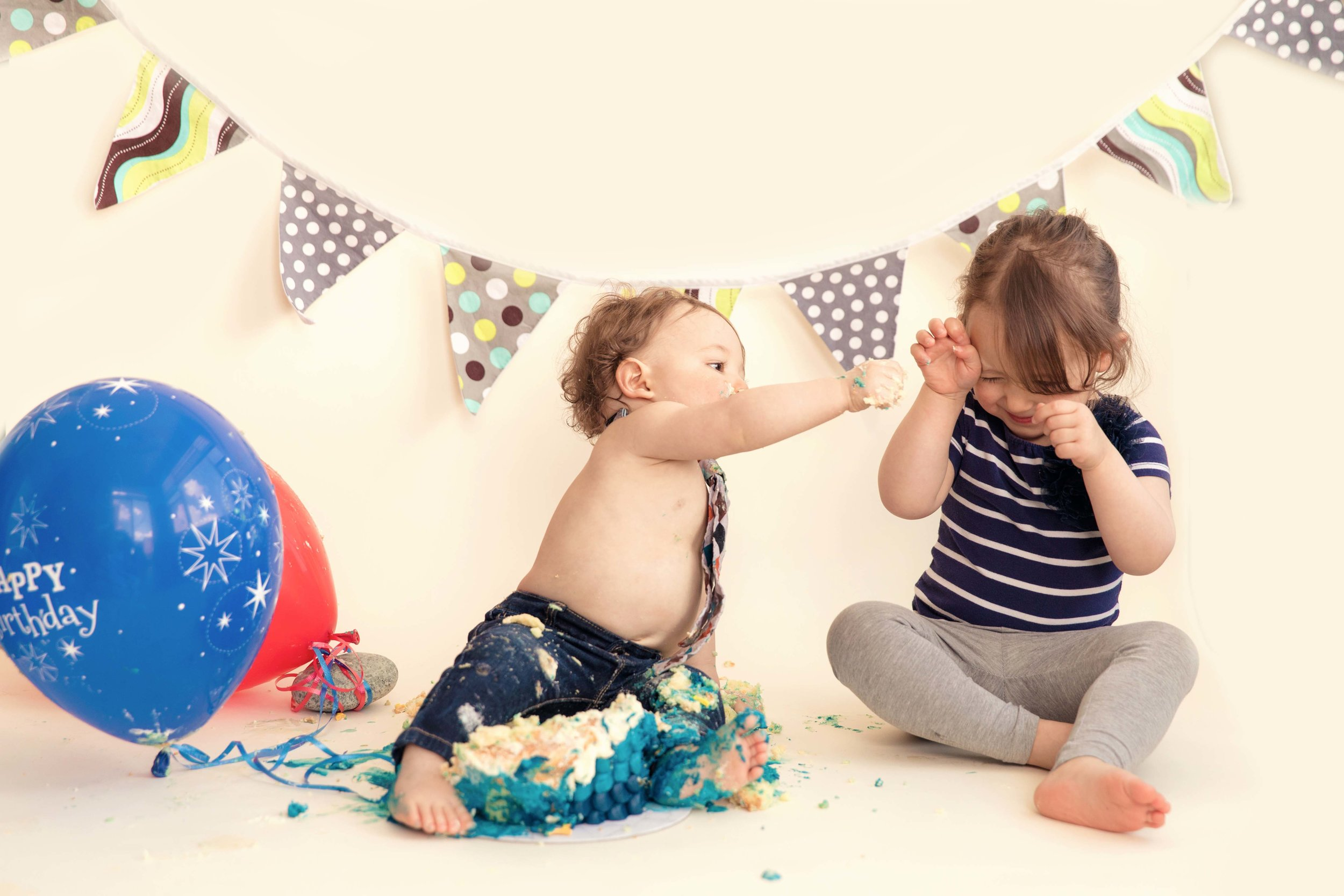 1 year old birthday boy is sharing his smashed cake with his 2 year old sister. Calgary cakesmash photographer